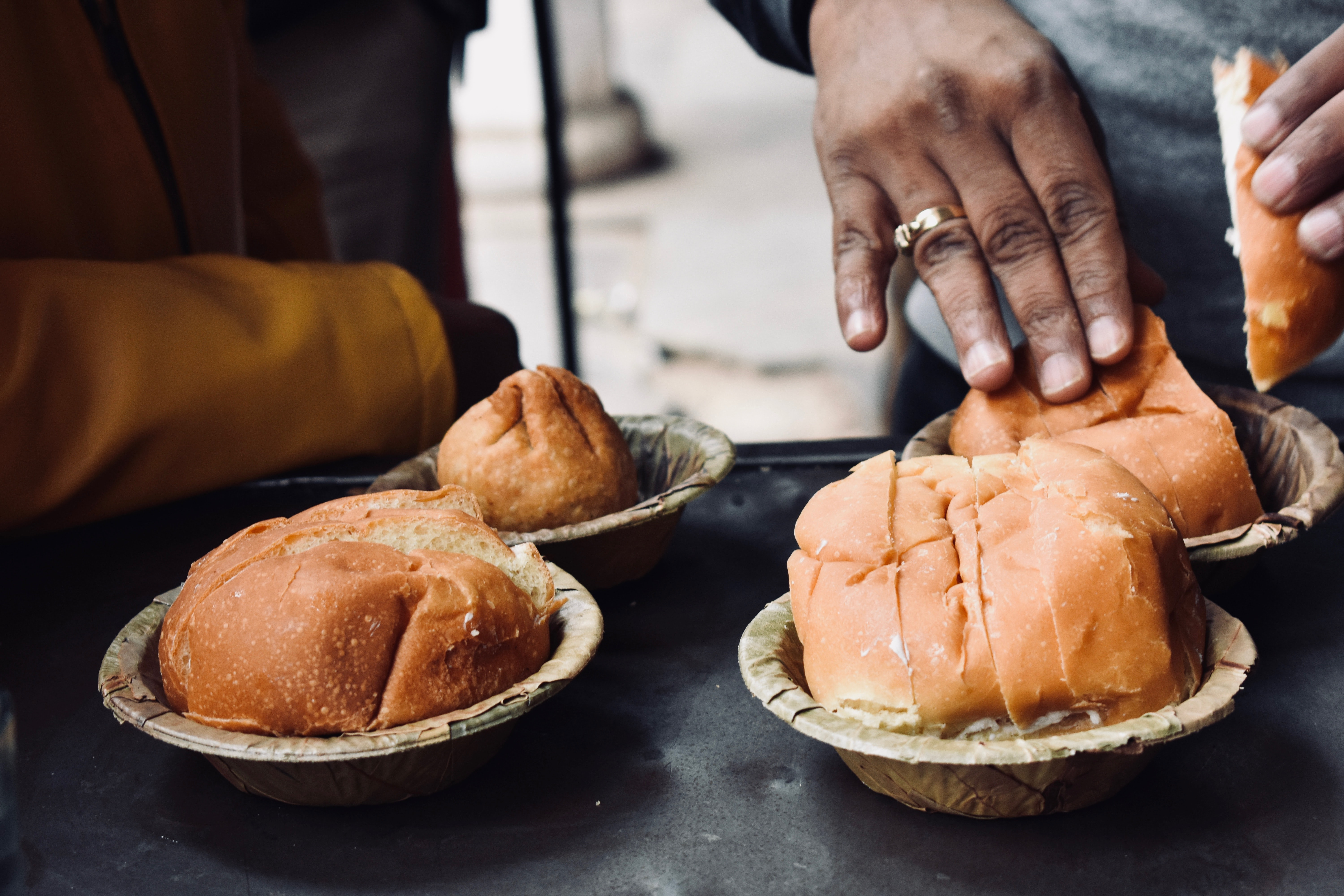 person holding bread on bowl at daytime