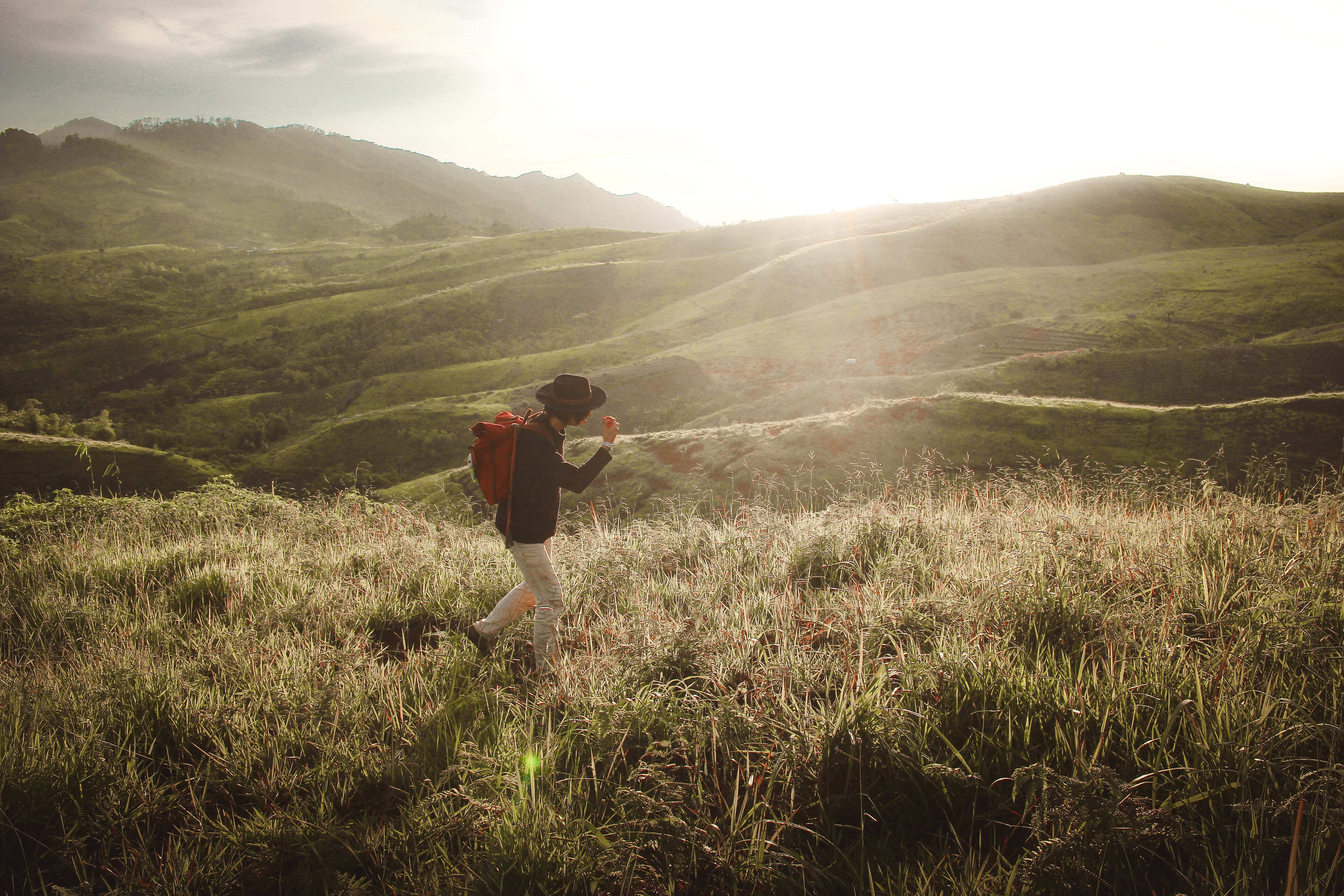 person walking in the middle of mountain grass field
