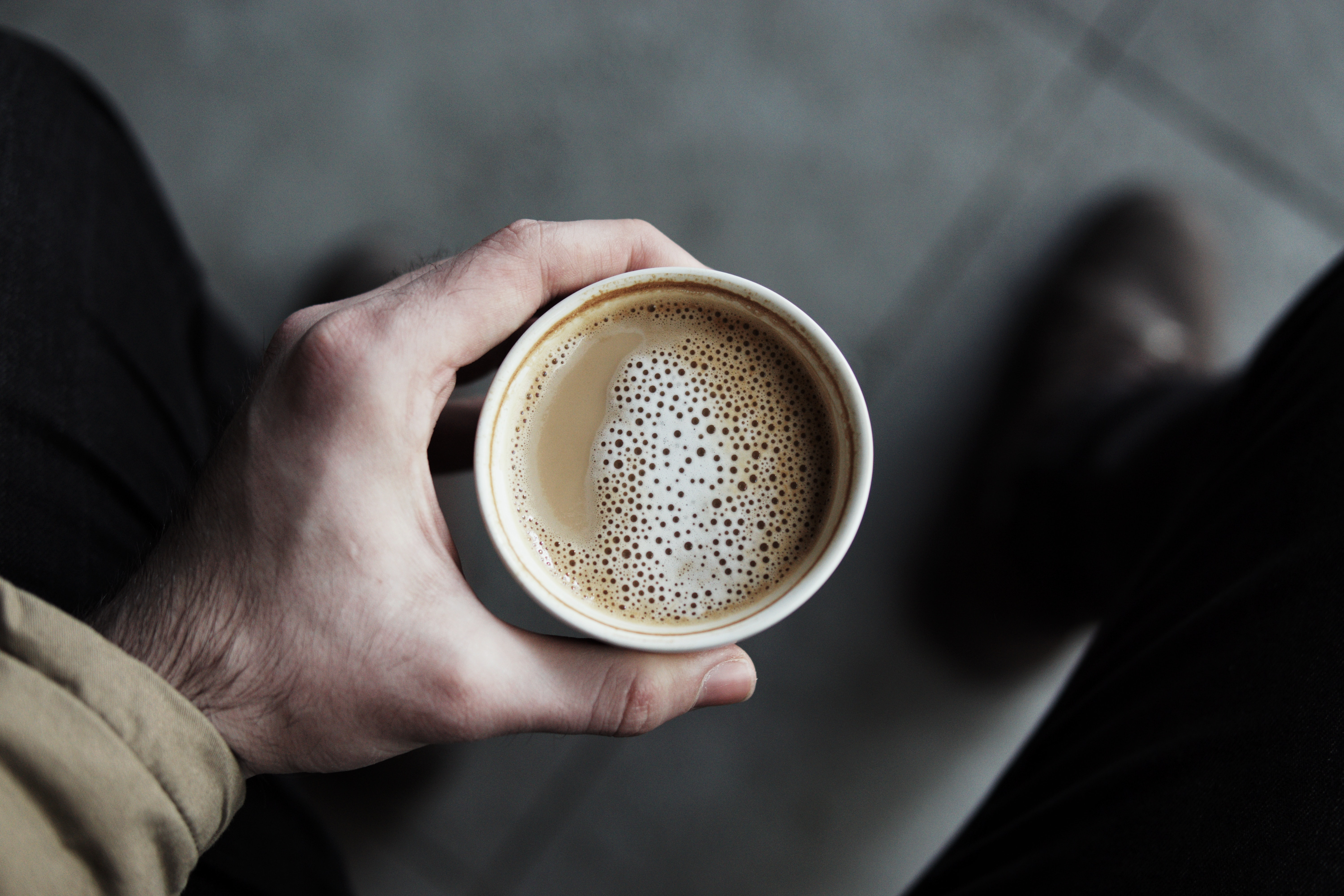person holding white paper cup filled with coffee