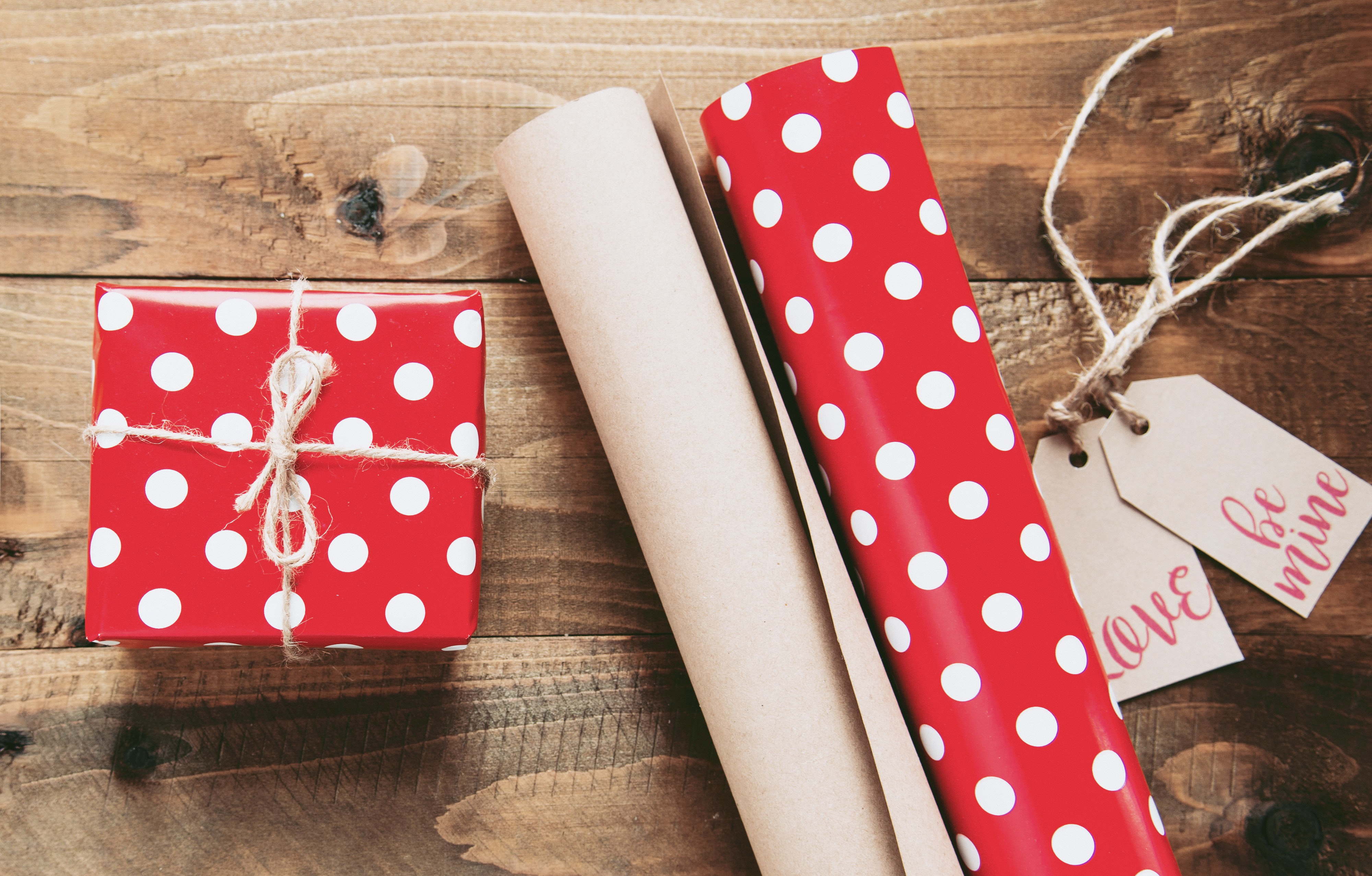 red and white polka-dot gift box beside gift wrappers