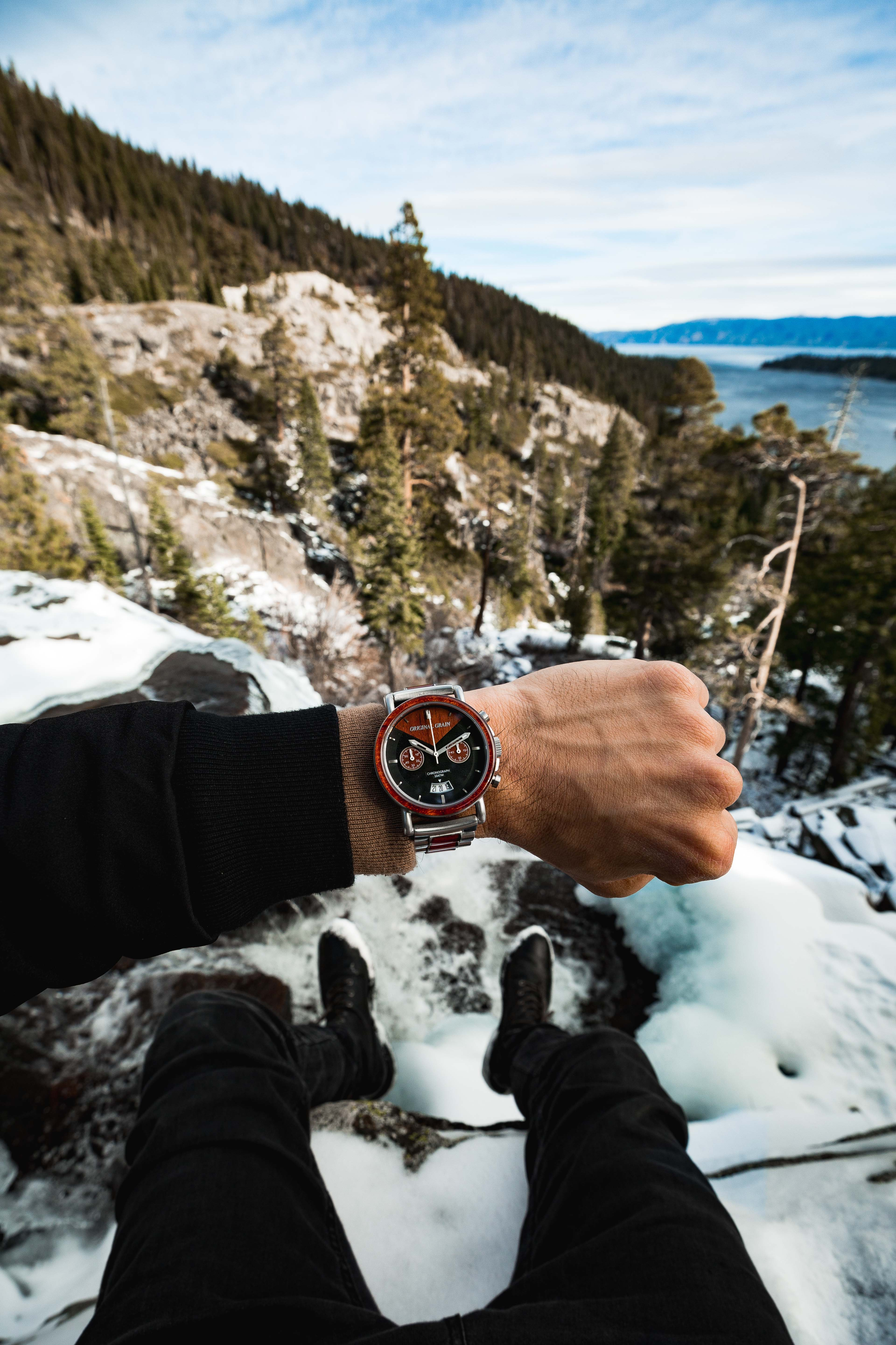 person wearing chronograph watch on top of mountain