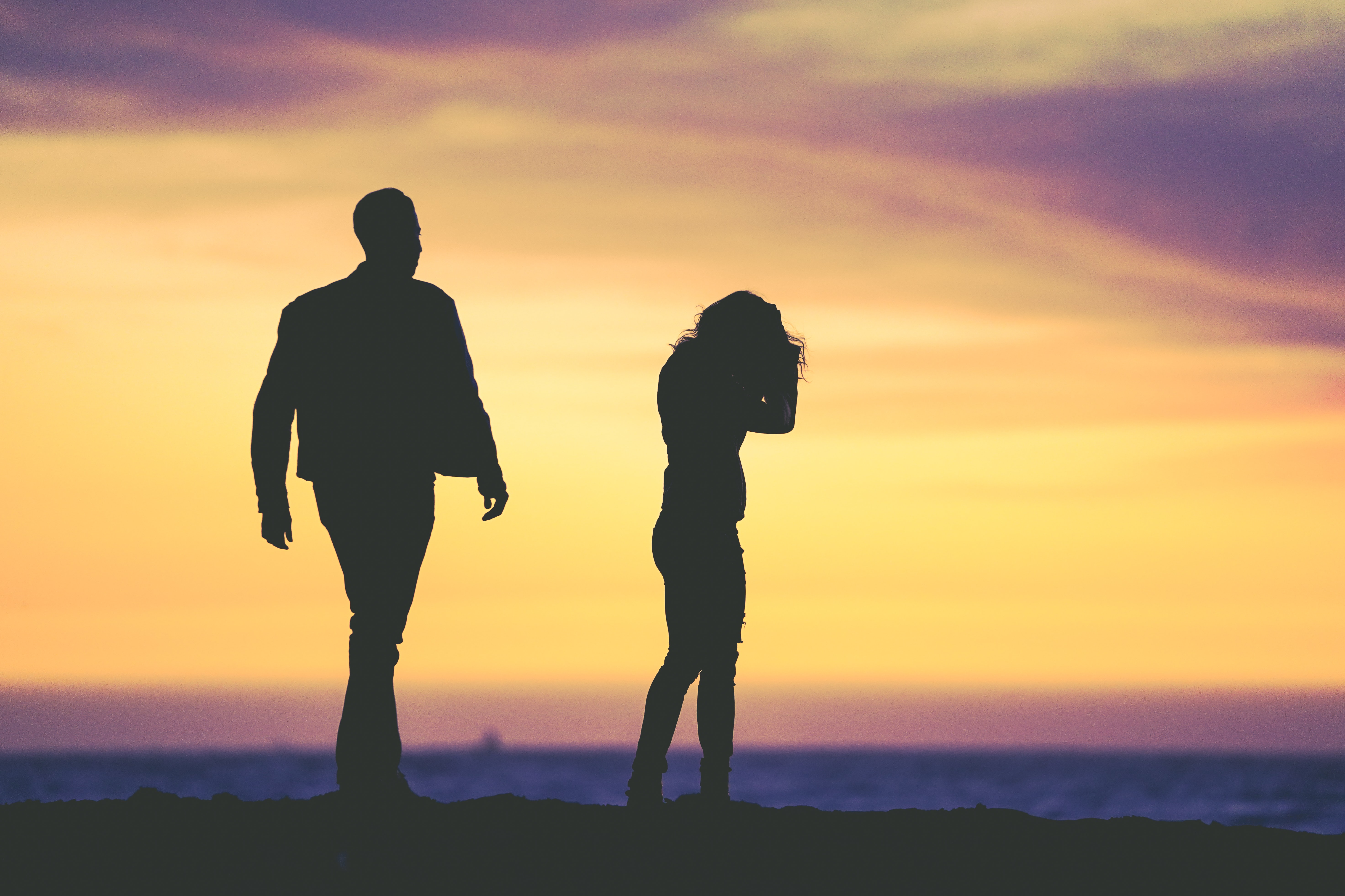 silhouette of man and woman under yellow sky