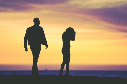 Silhouette of a man and woman having an argument.