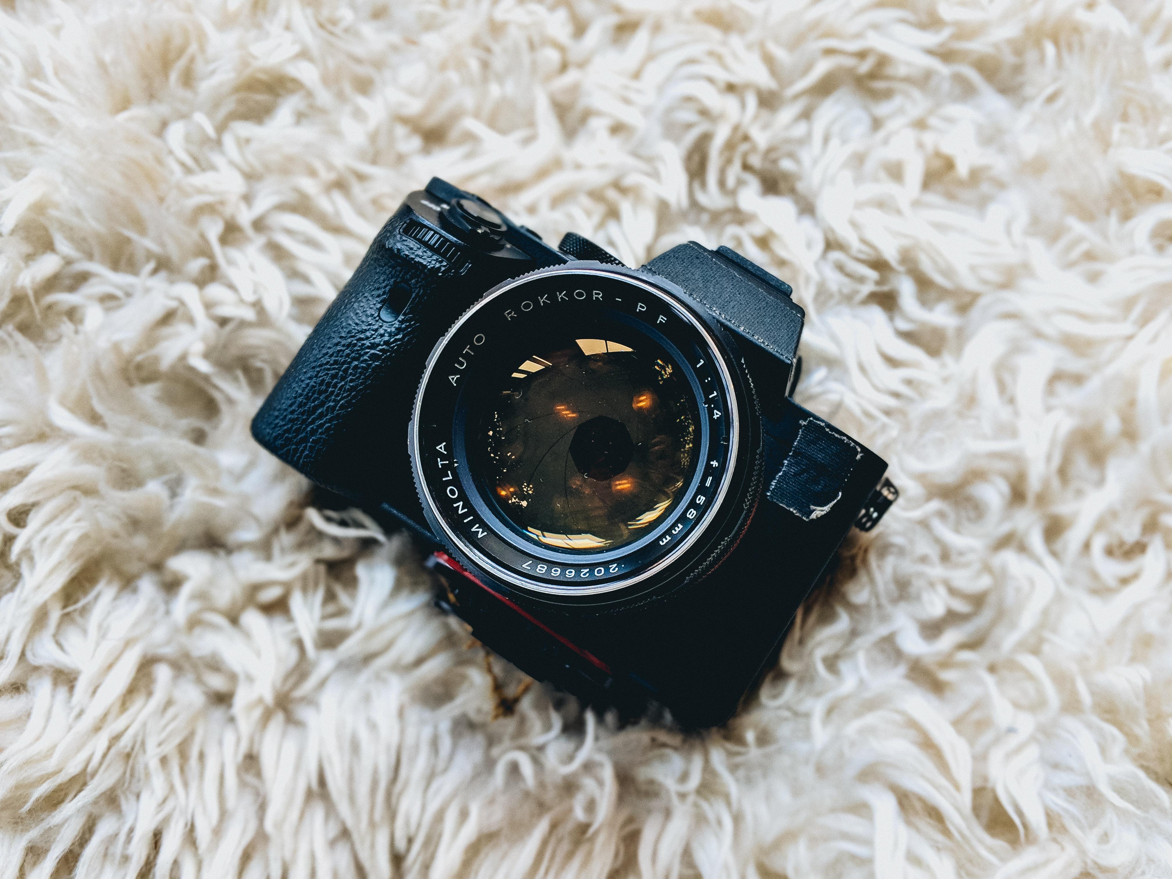 black milc camera on white fur cloth