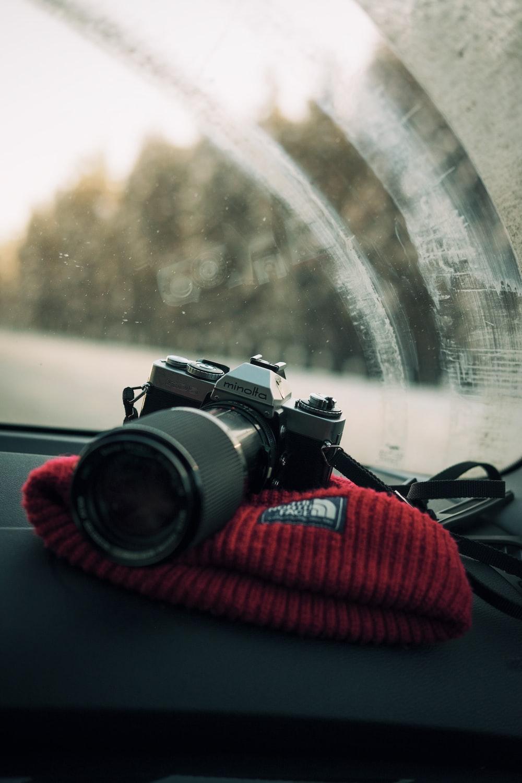 photo of gray Minolta DSLR camera on glove compartment