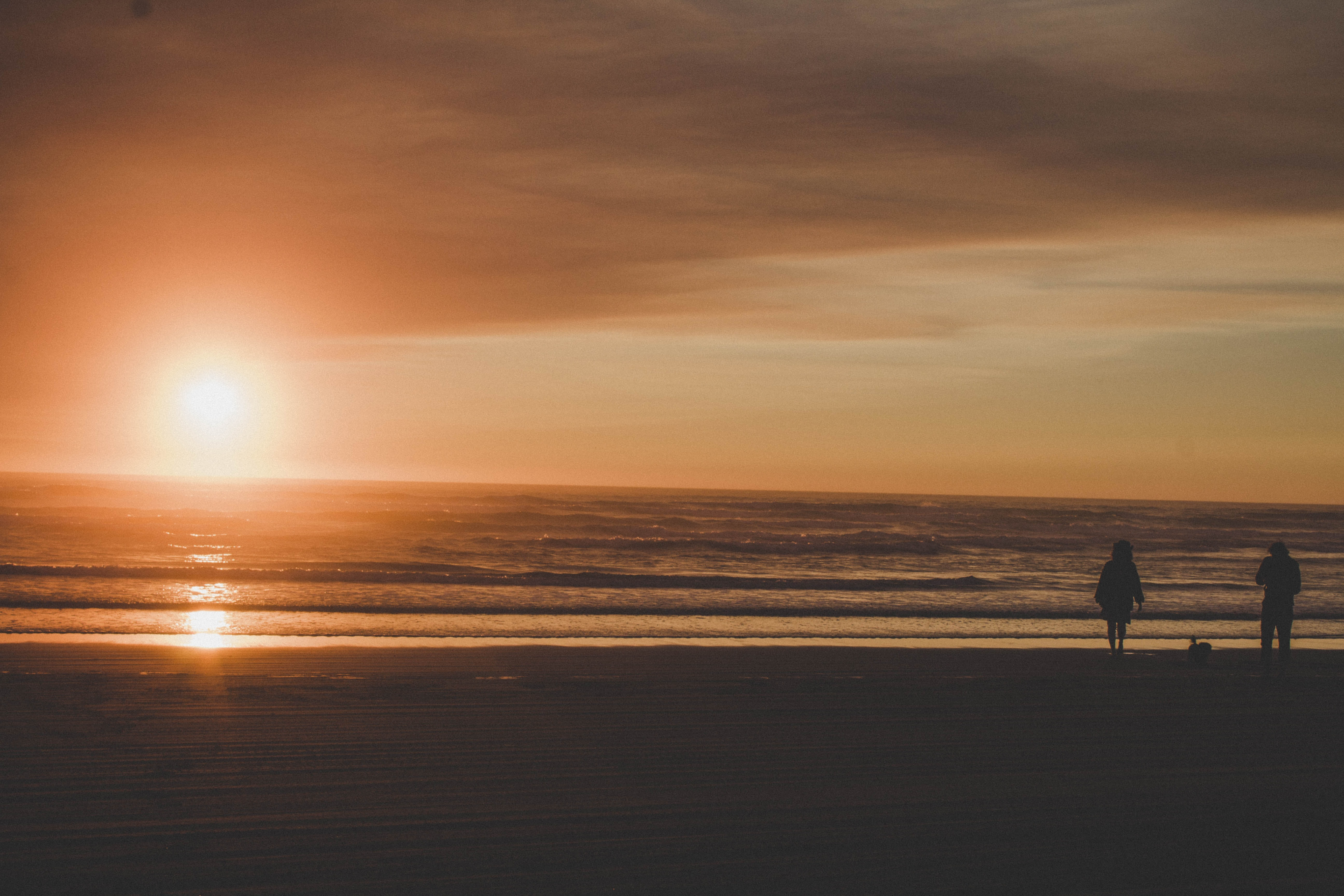 silhouette photography of person standing while facing body of water during sunset