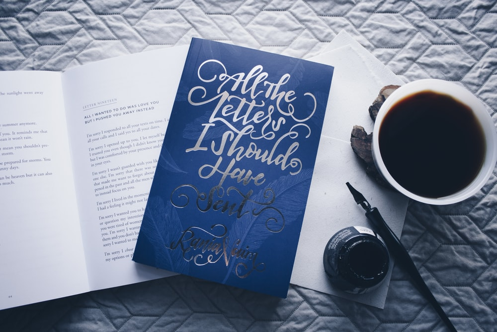 closed All the Letters I Should Have Sent novel book beside filled white cup