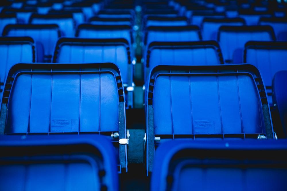 Image description: vivid blue seats inside of a stadium.