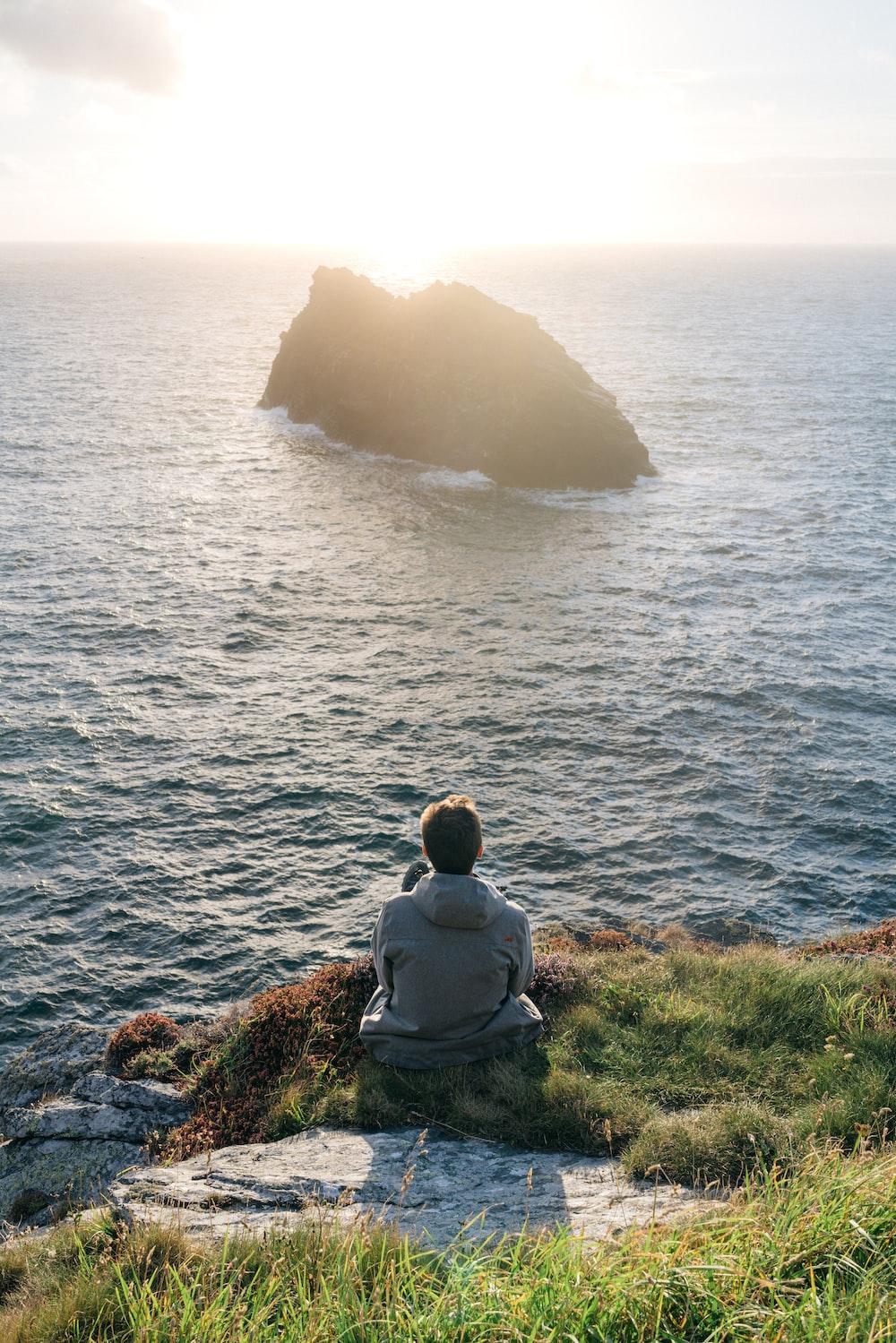 man sitting on grass beside ocean during daytime