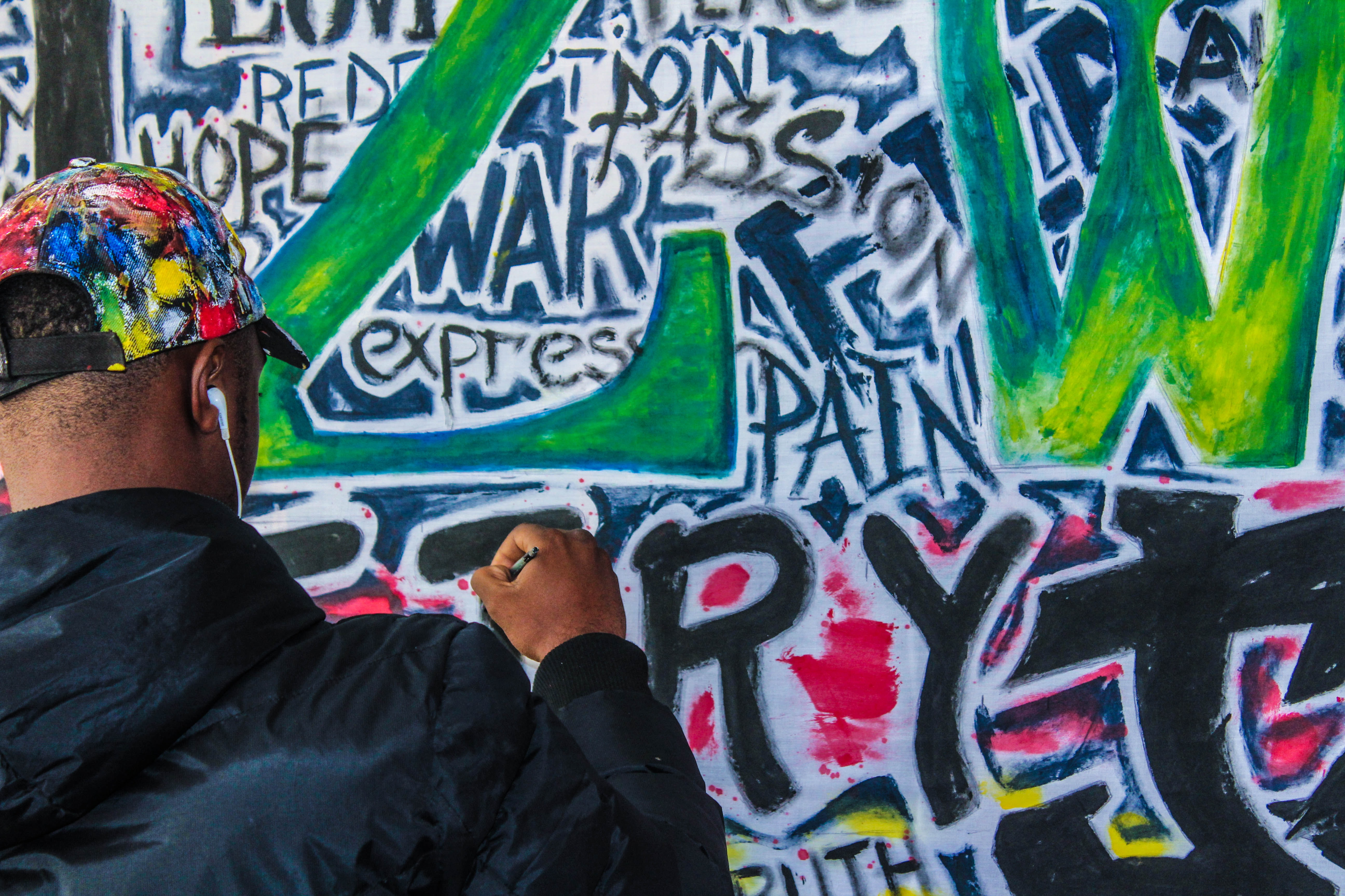 man wearing black jacket painting graffiti