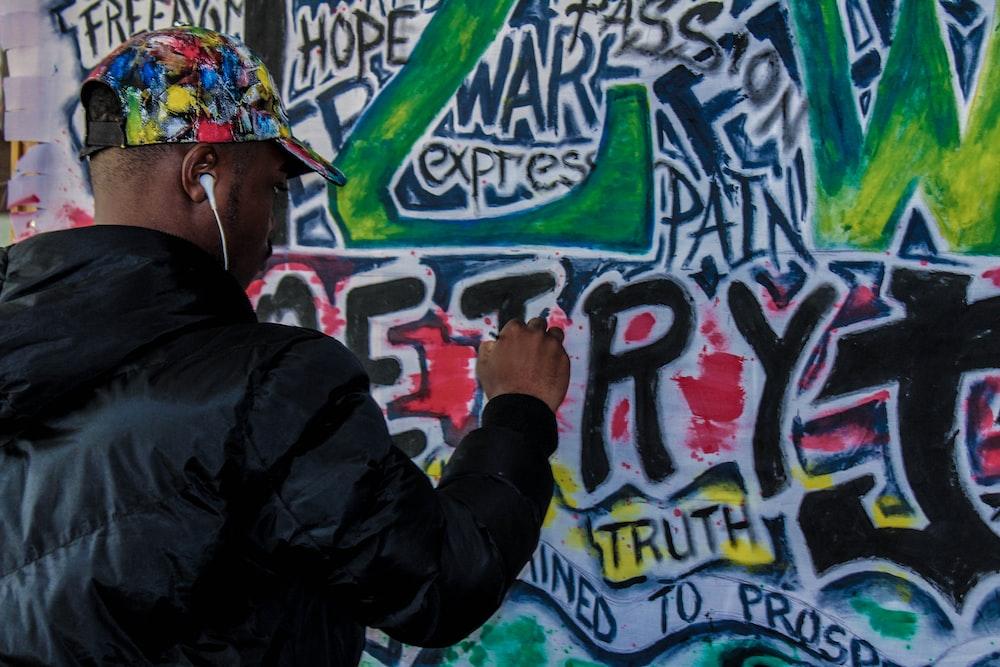 man spraying graffiti on wall during daytime