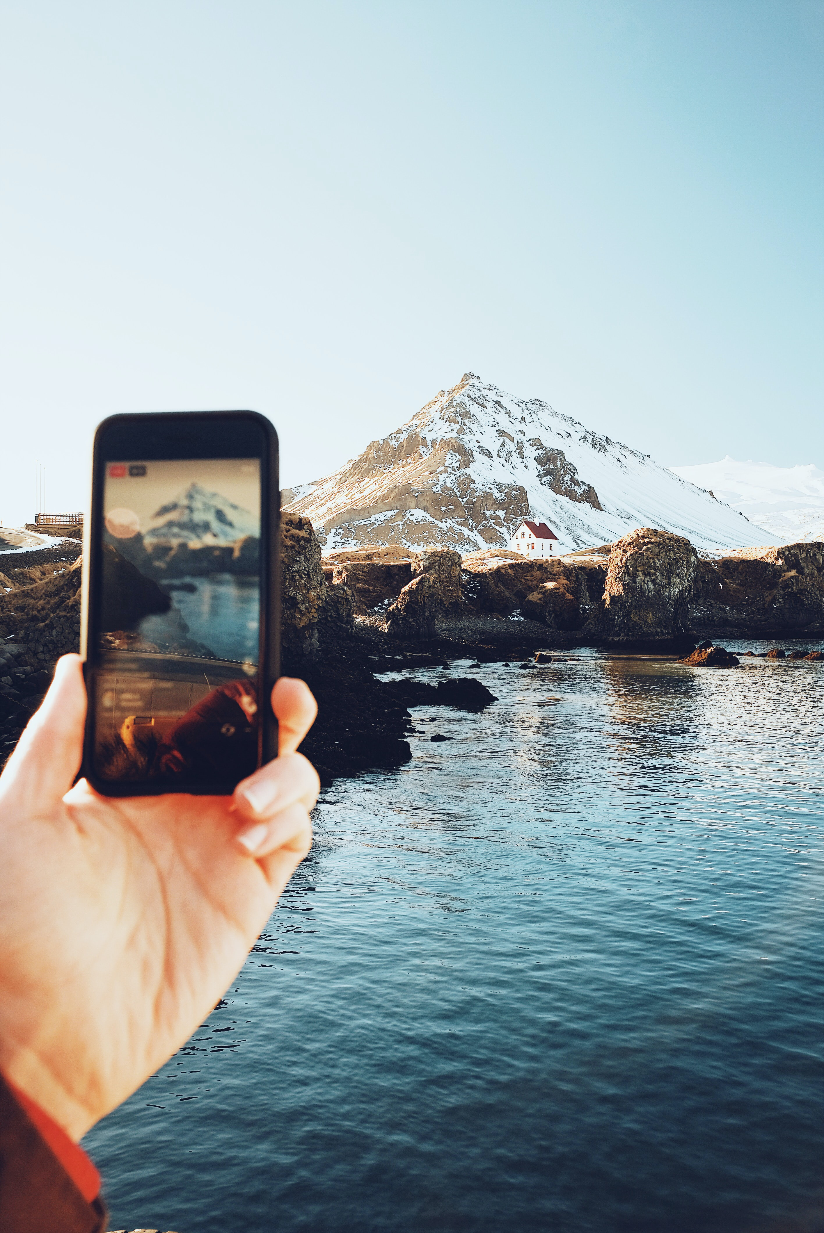 person taking picture on mountain covered with snow
