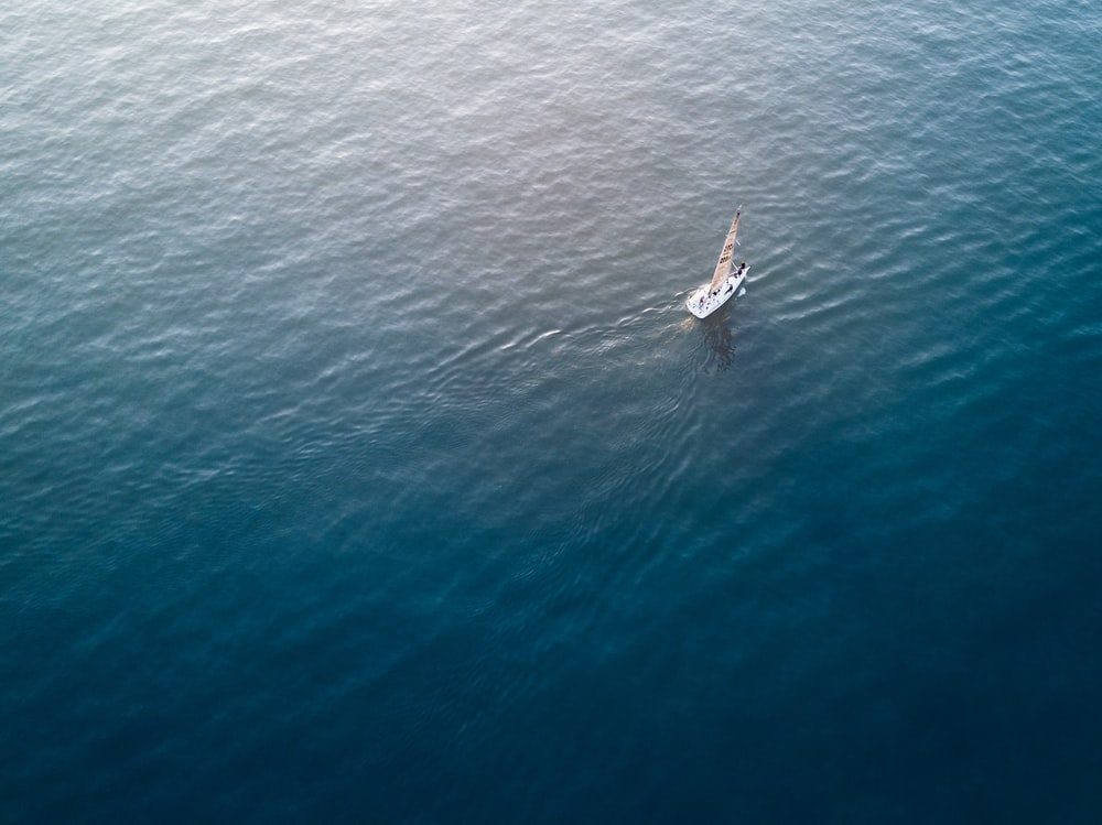 aerial photograph of white sailboat on calm body of water