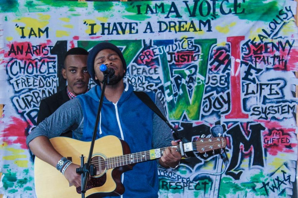 man playing acoustic guitar while singing