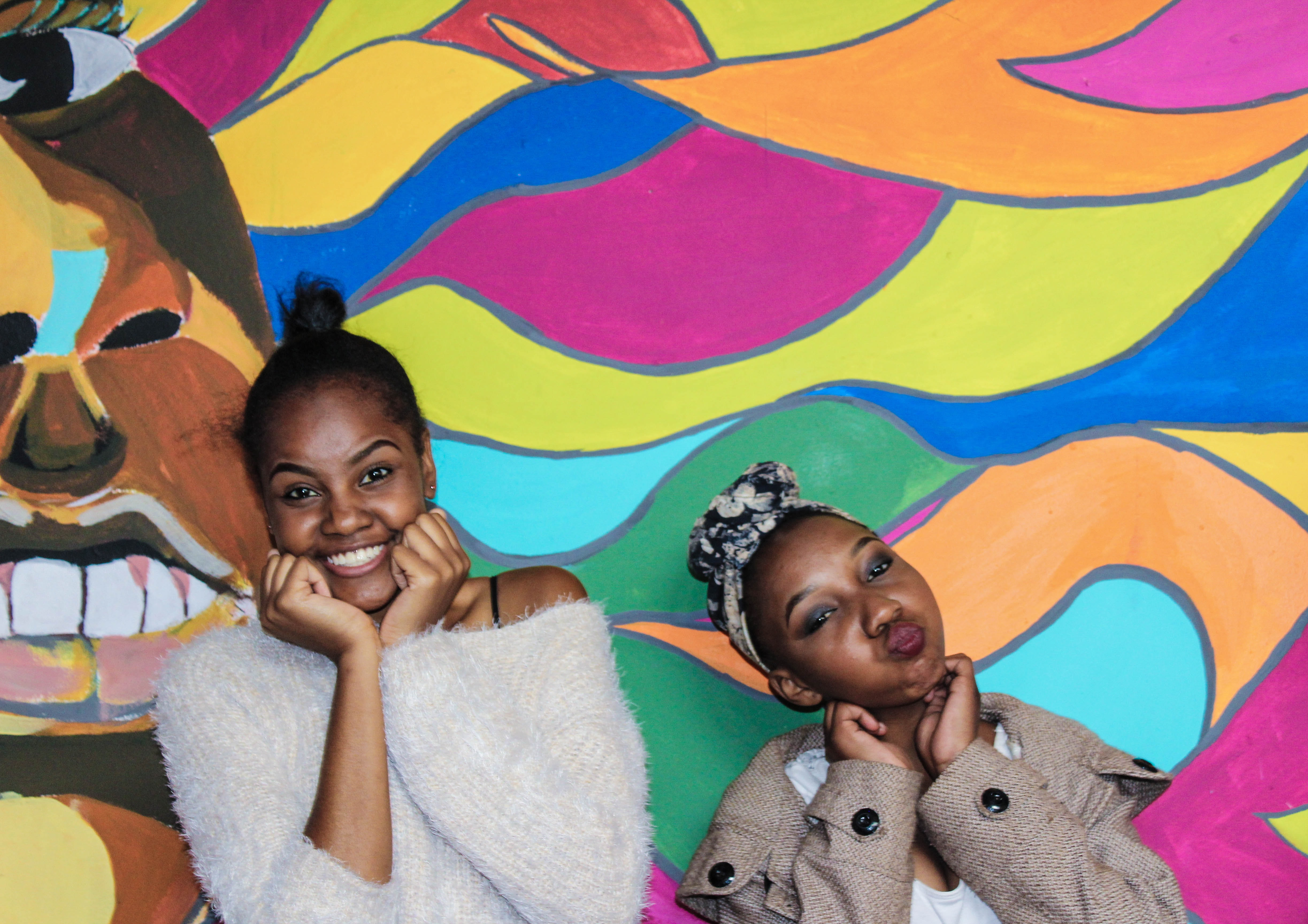 two girl's posing at multicolored wall