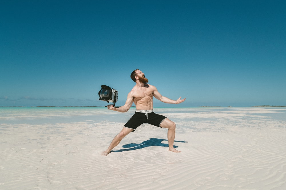 man holding camera on seashore