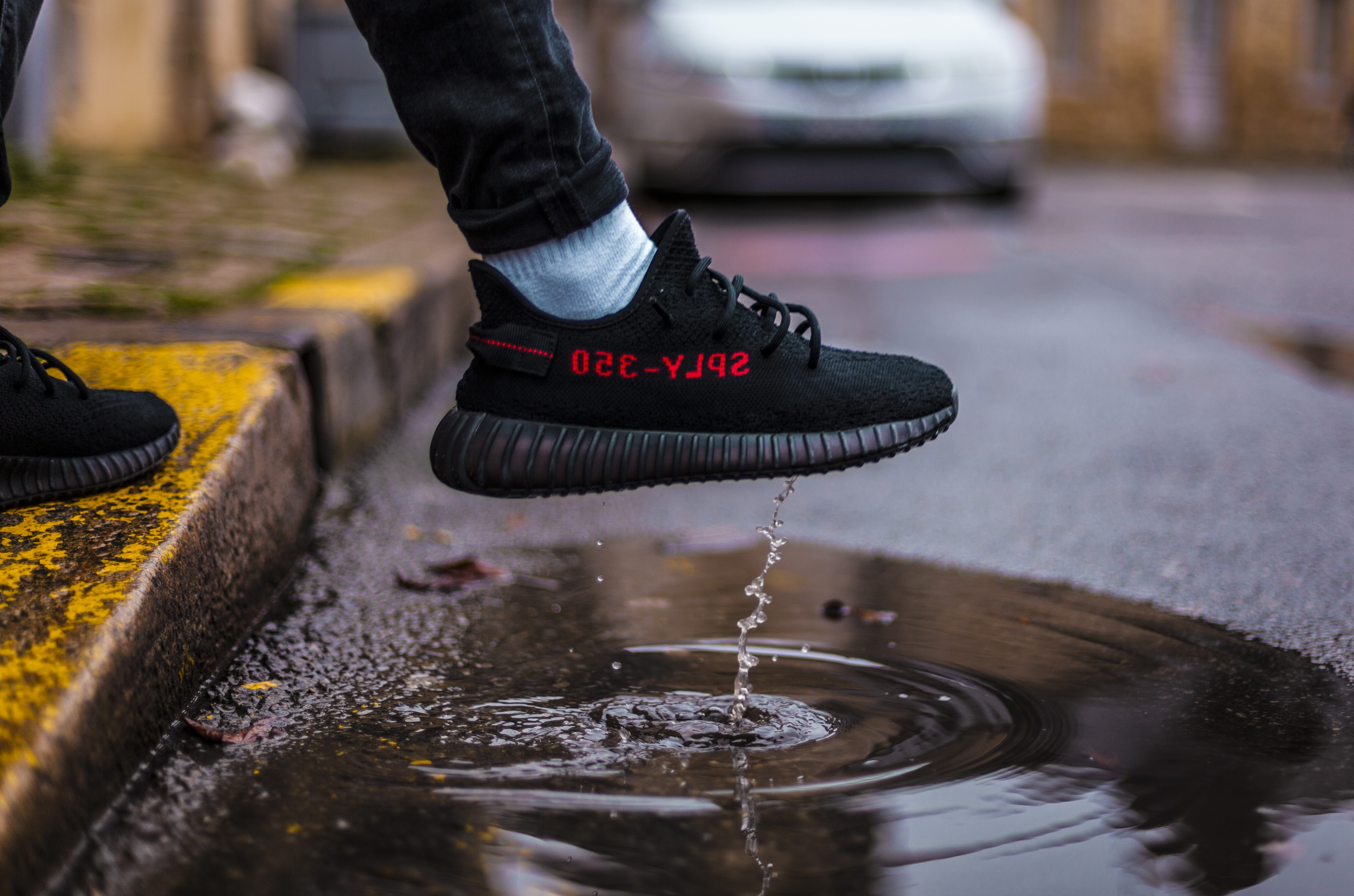 person wearing adidas Yeezy Boost 350 shoe above road puddle