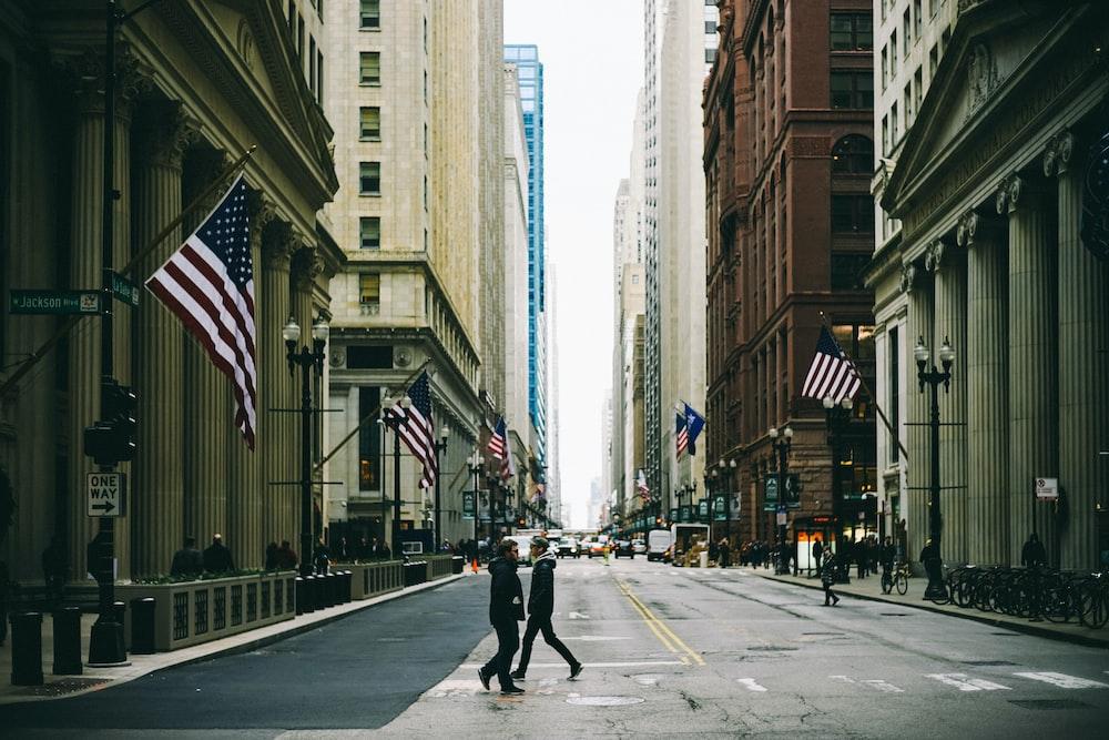 people walking on street near flag of U.S. America