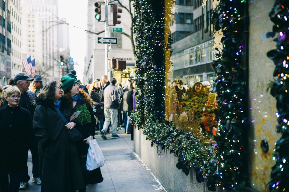 people in sidewalk staring at string lights
