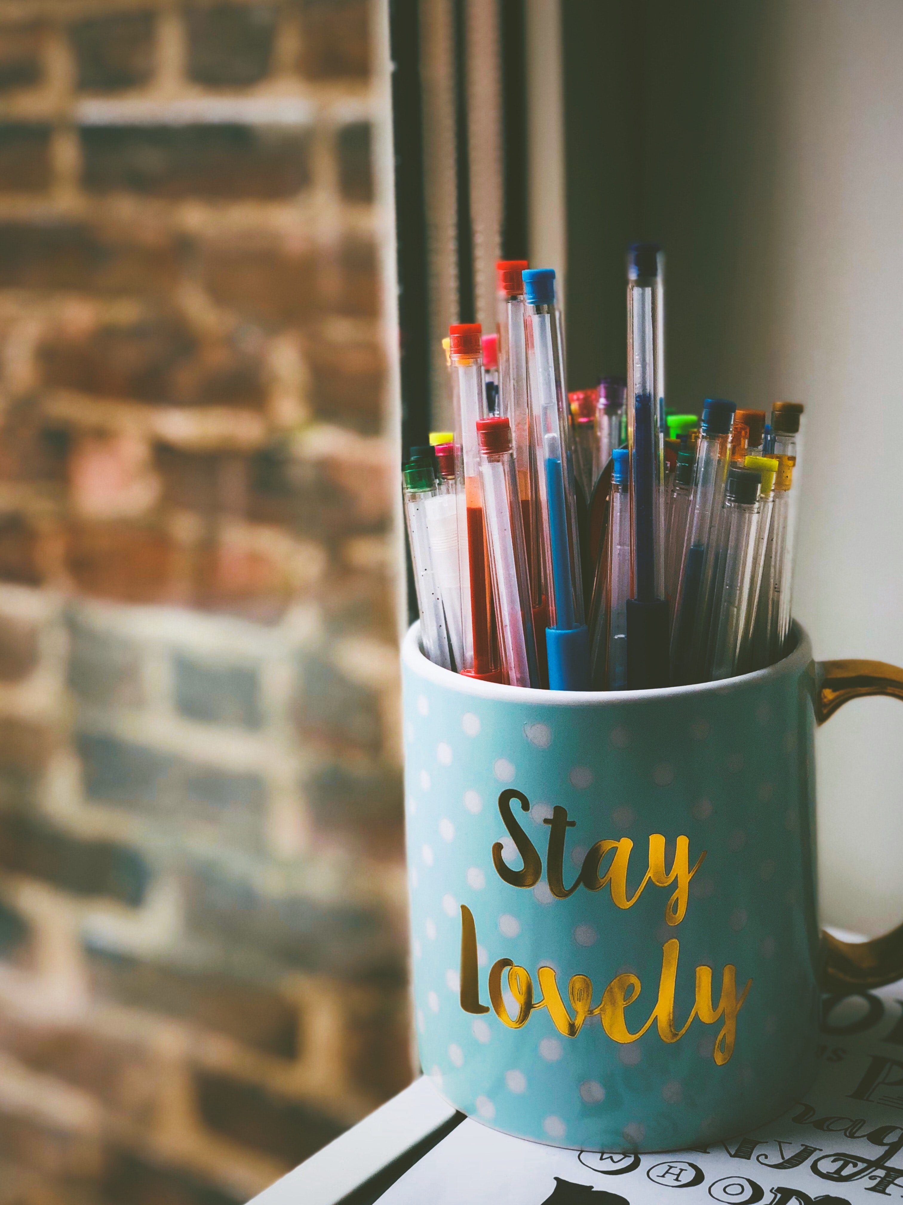 pens in blue ceramic mug in front of window during daytime