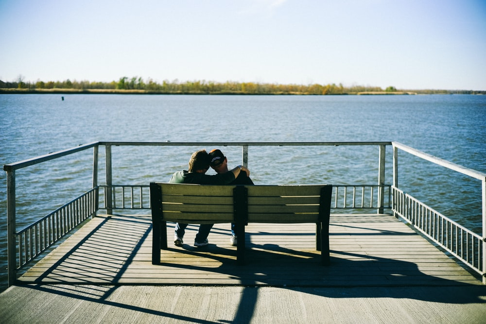 two person sitting on bench facing body of water