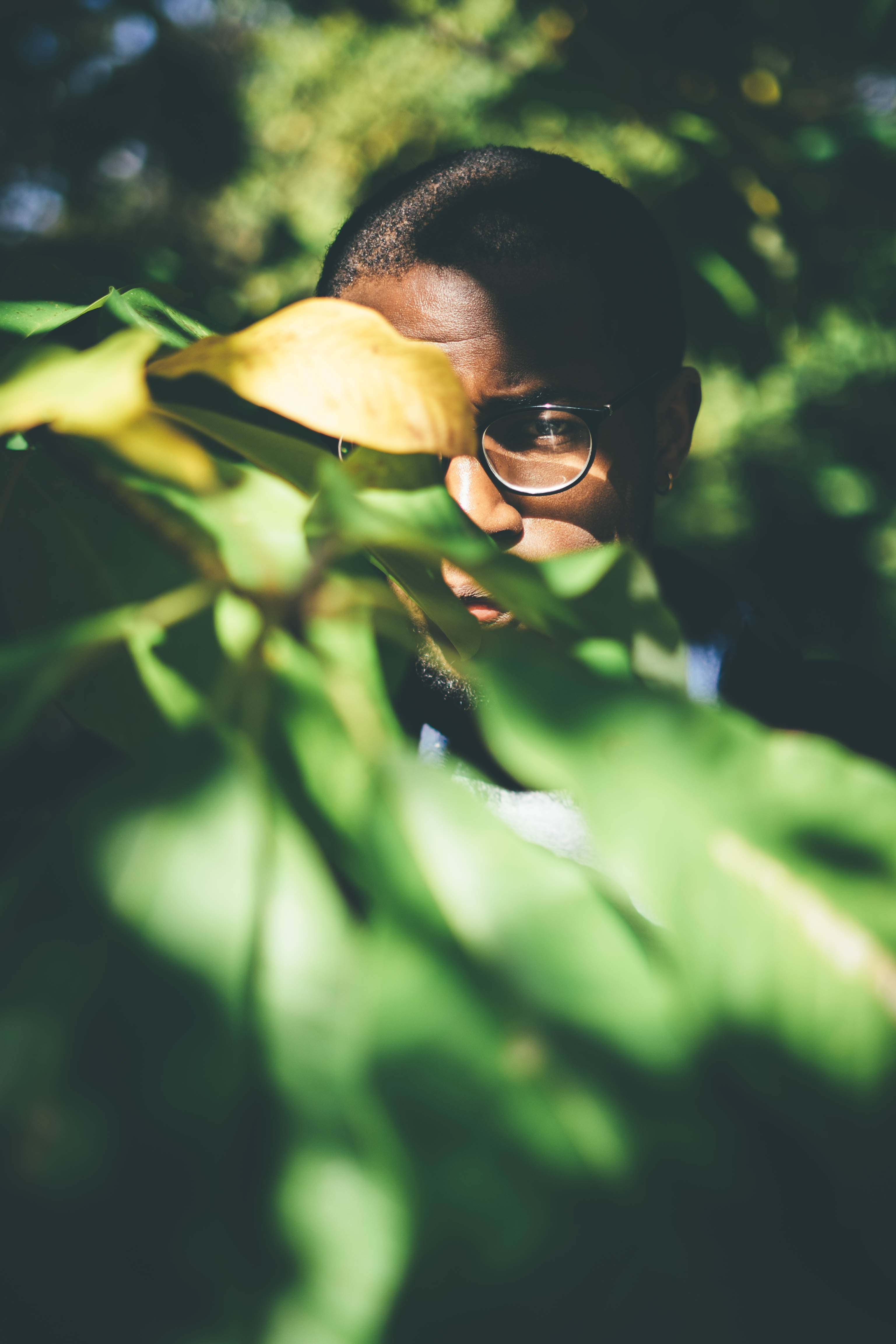 man in black eyeglasses behind plant leaf at daytime