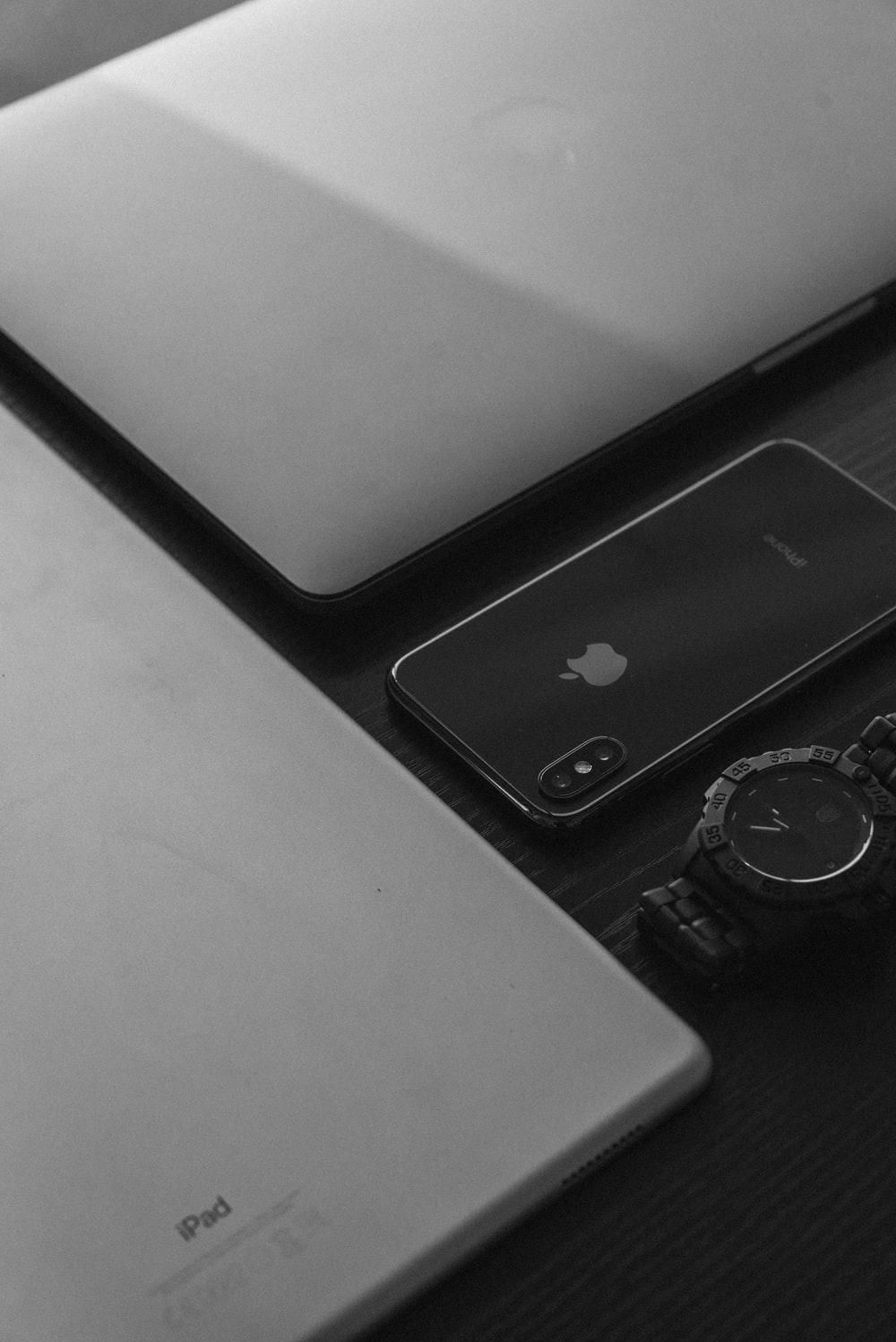 silver Apple MacBook, silver iPad, space gray iPhone X, and black analog watch