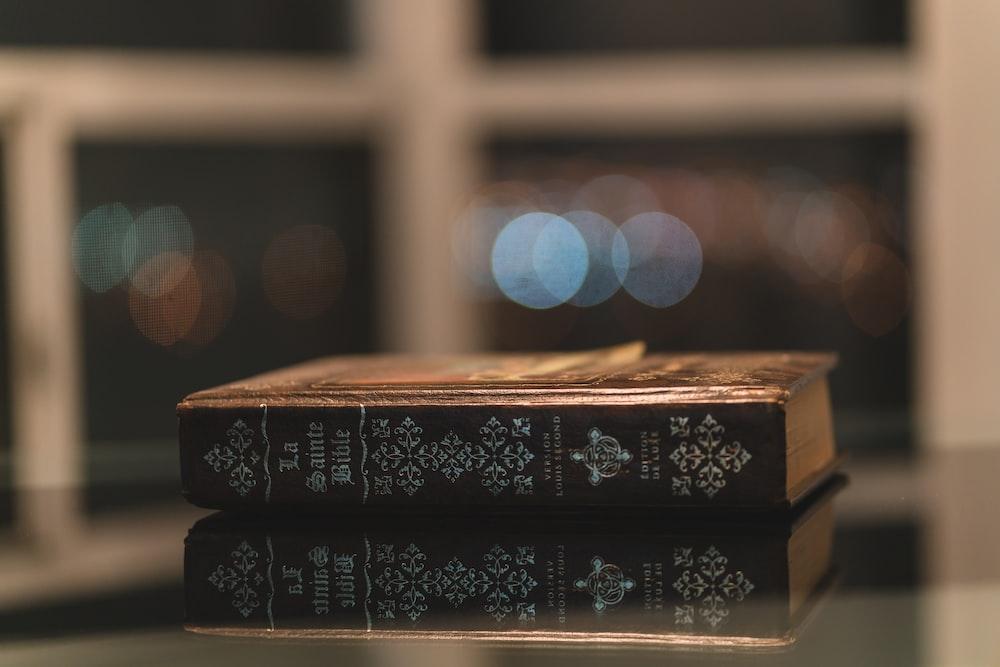 selective focus photography of brown hardbound book