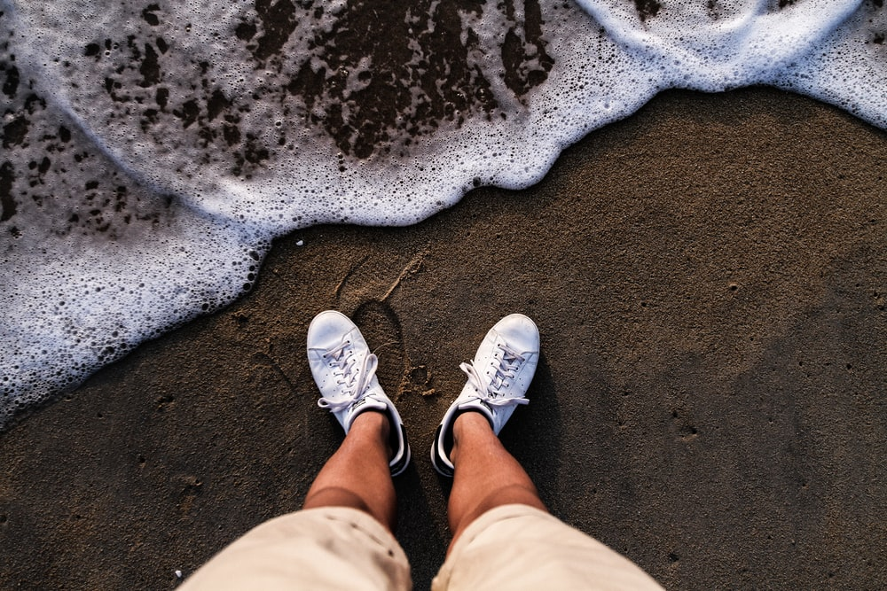 person wearing white shoes standing on sea shore
