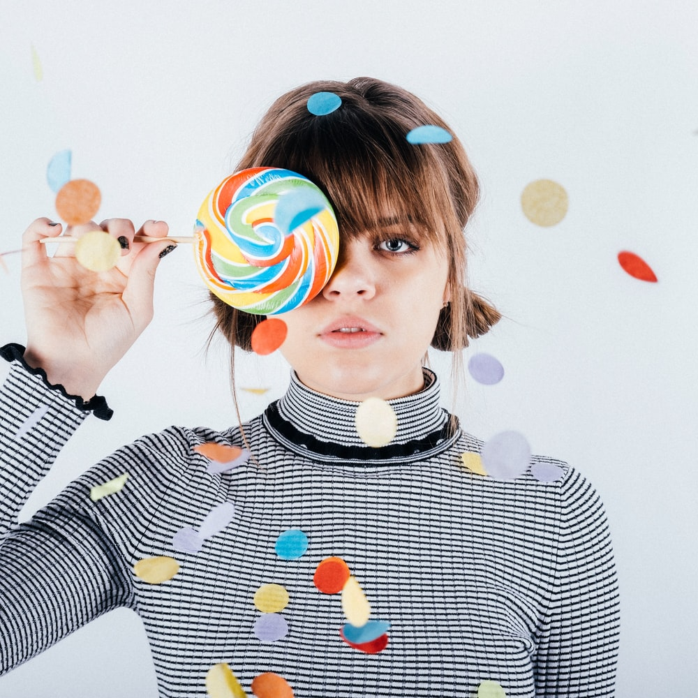 woman covering her right eye with lollipop
