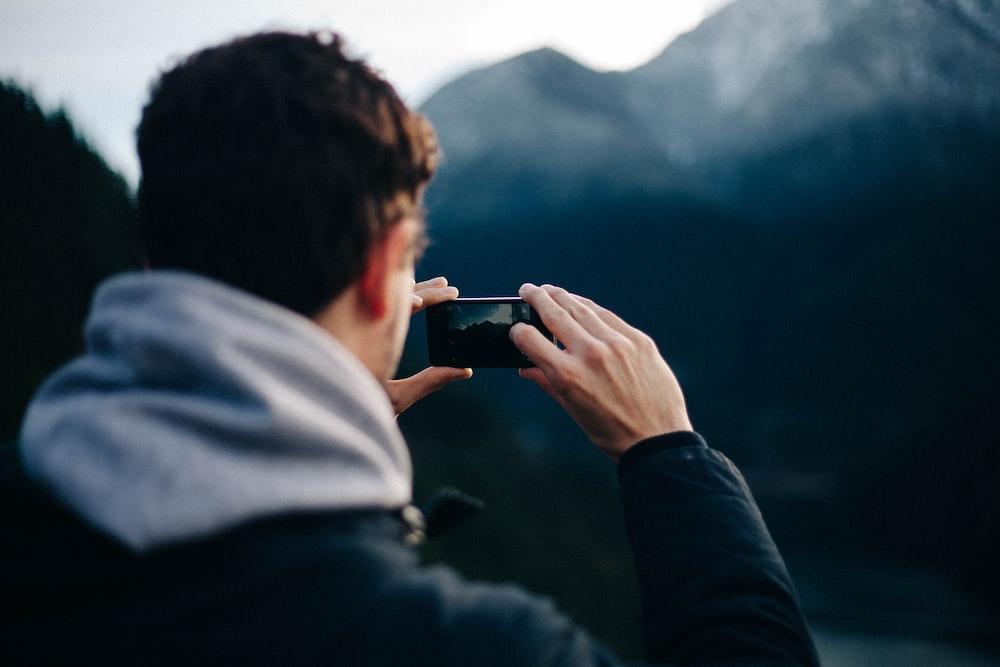 man holding smartphone taking photo of mountain