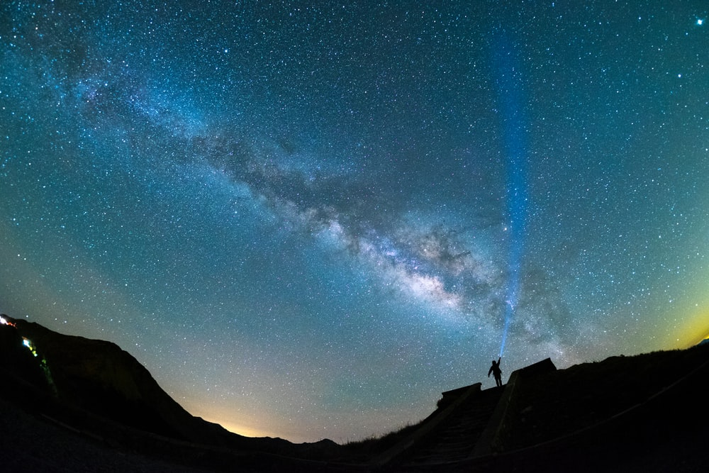 silhouette of man raising hands above starry sky