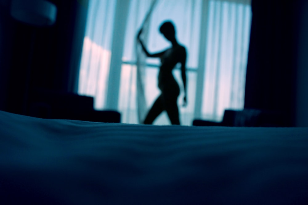 sillouehtte photo of woman standing beside window curtains