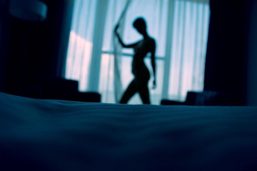 窓のカーテンの横に立っている女性のsillouehtte写真