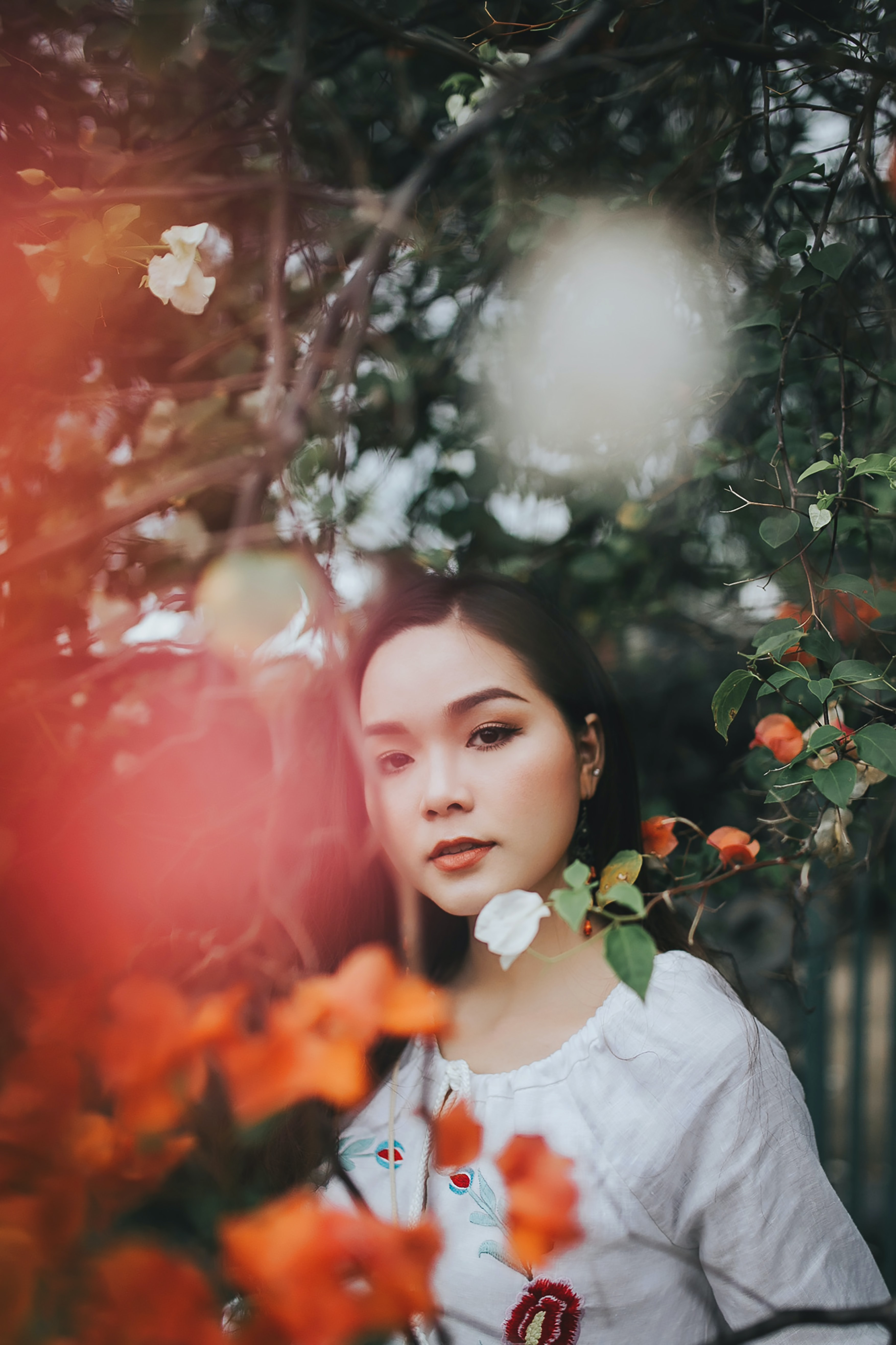selective focus photo of woman wearing white top beside trees