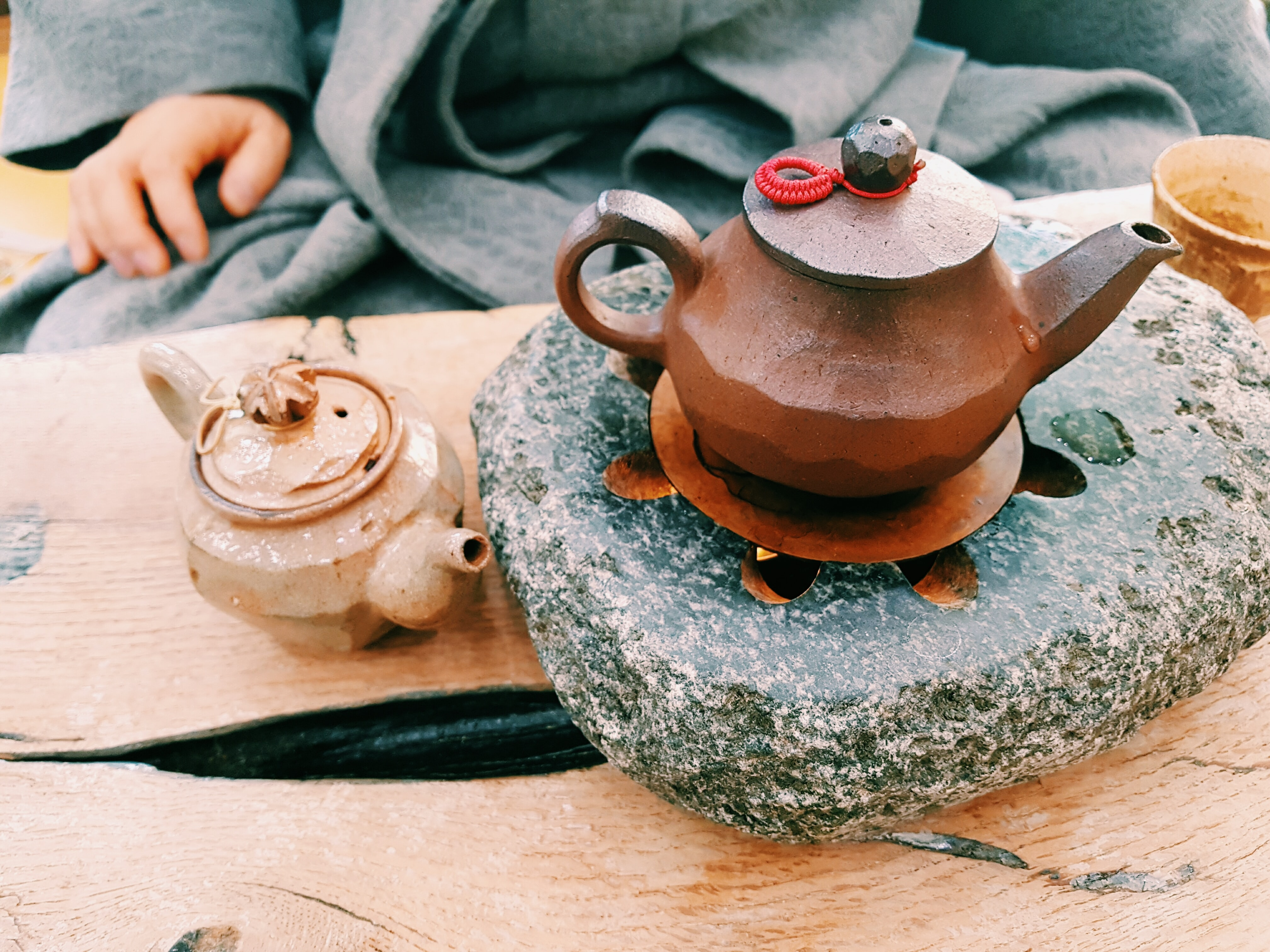 brown clay teapot on heated stone