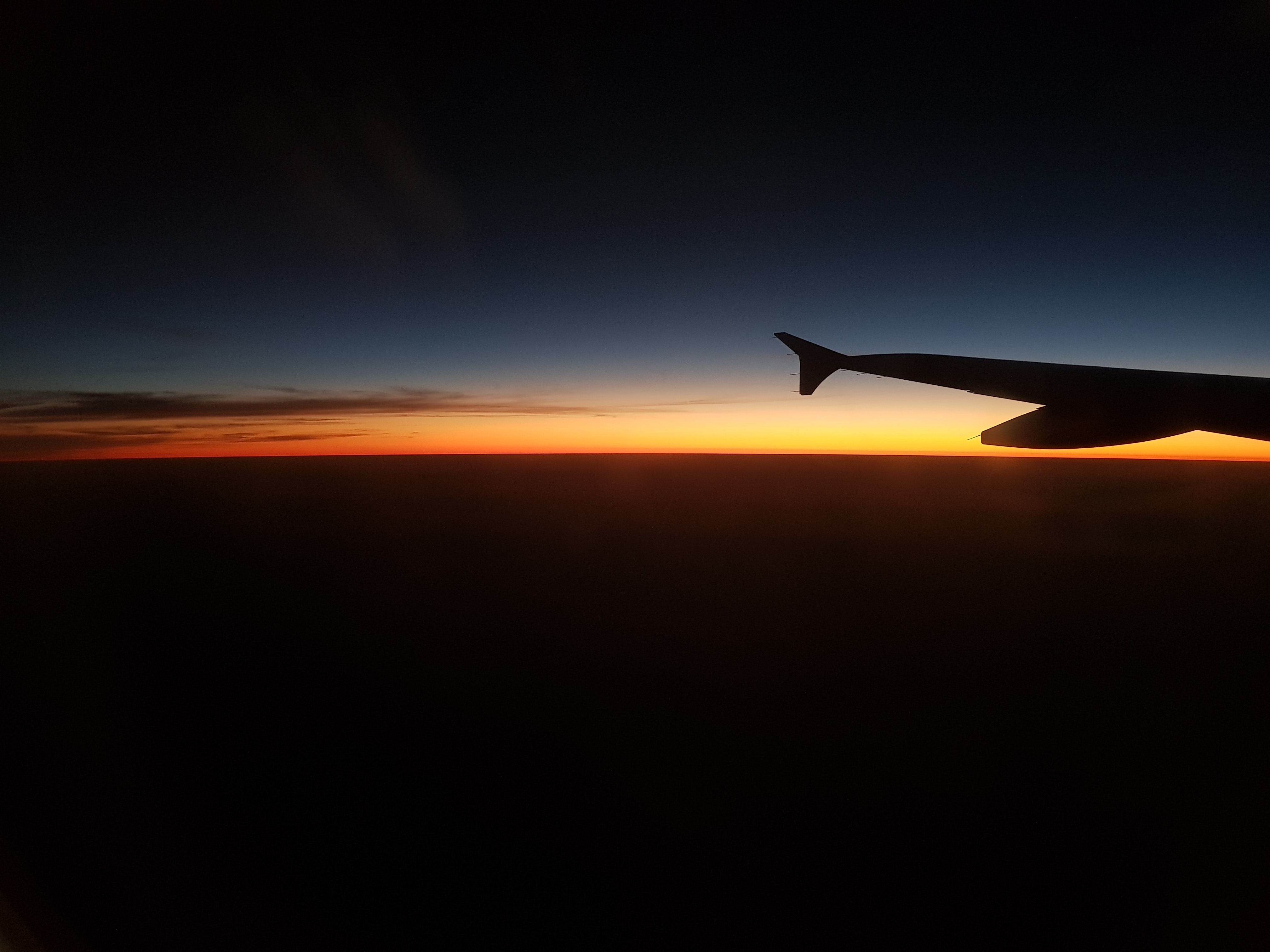 silhouette photograph of plane wing during golden hour