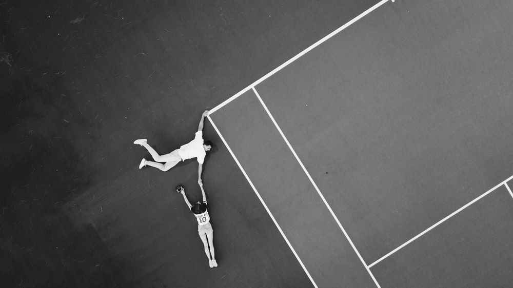 grayscale photography of woman holding woman's hand on tennis court
