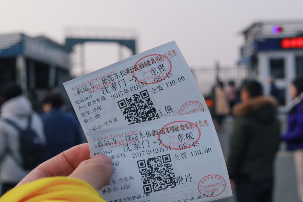 person holding two white tickets