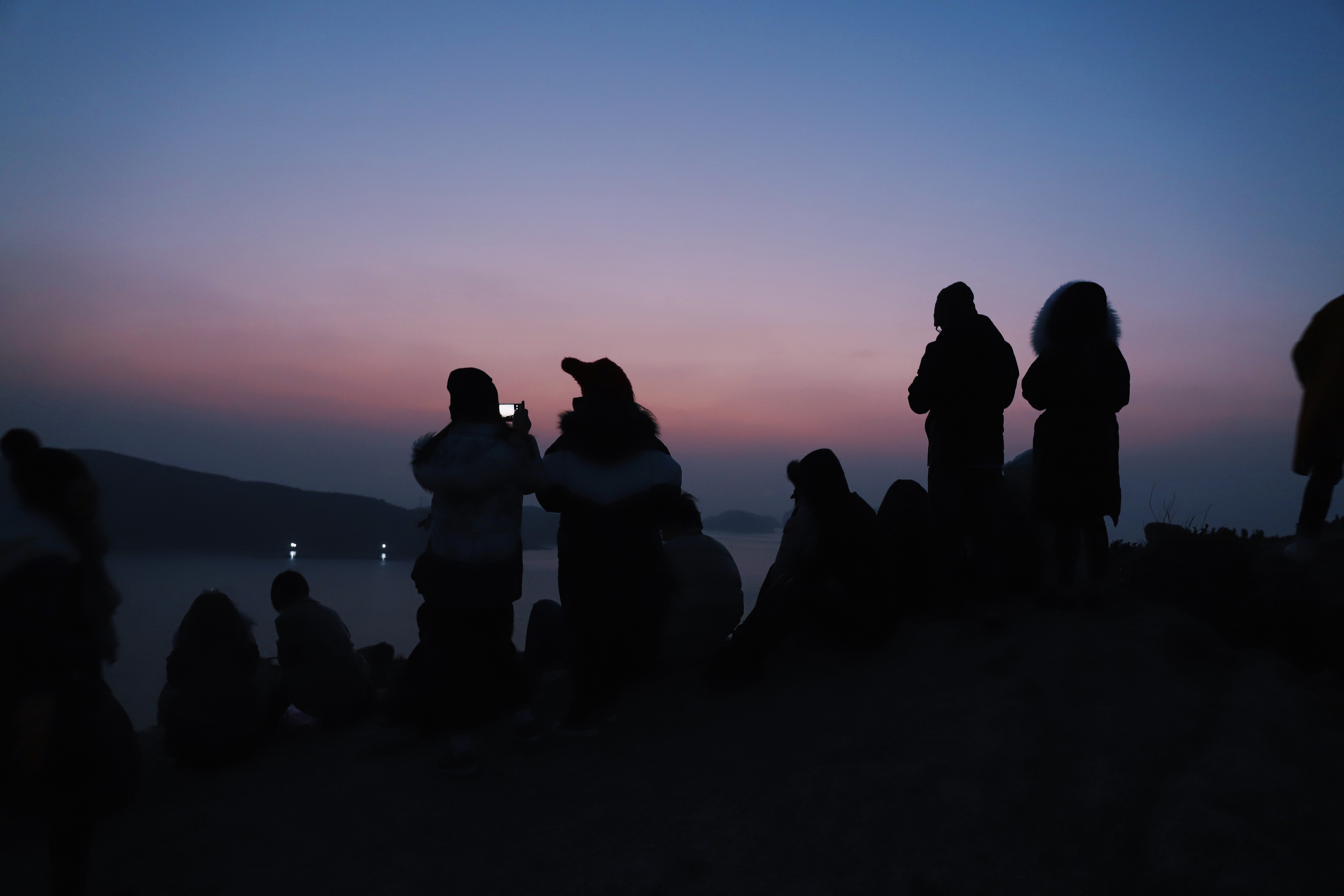 silhouette of people near body of water