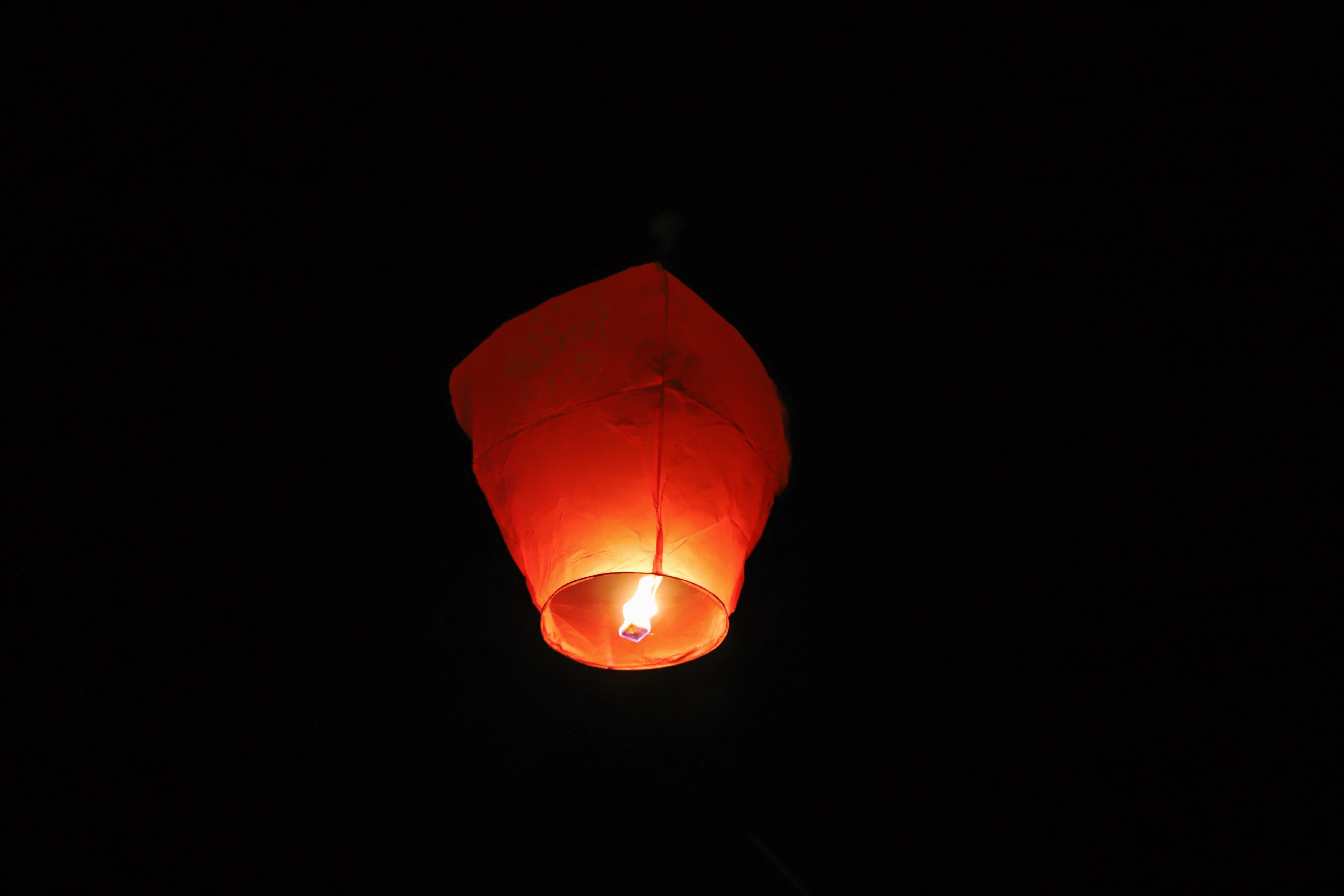 paper lantern with lighted candle in dark room