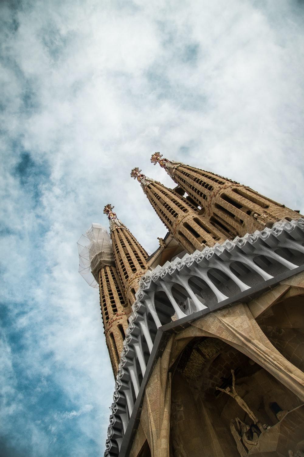 low-angle photography of concrete cathedral under cloudy sky