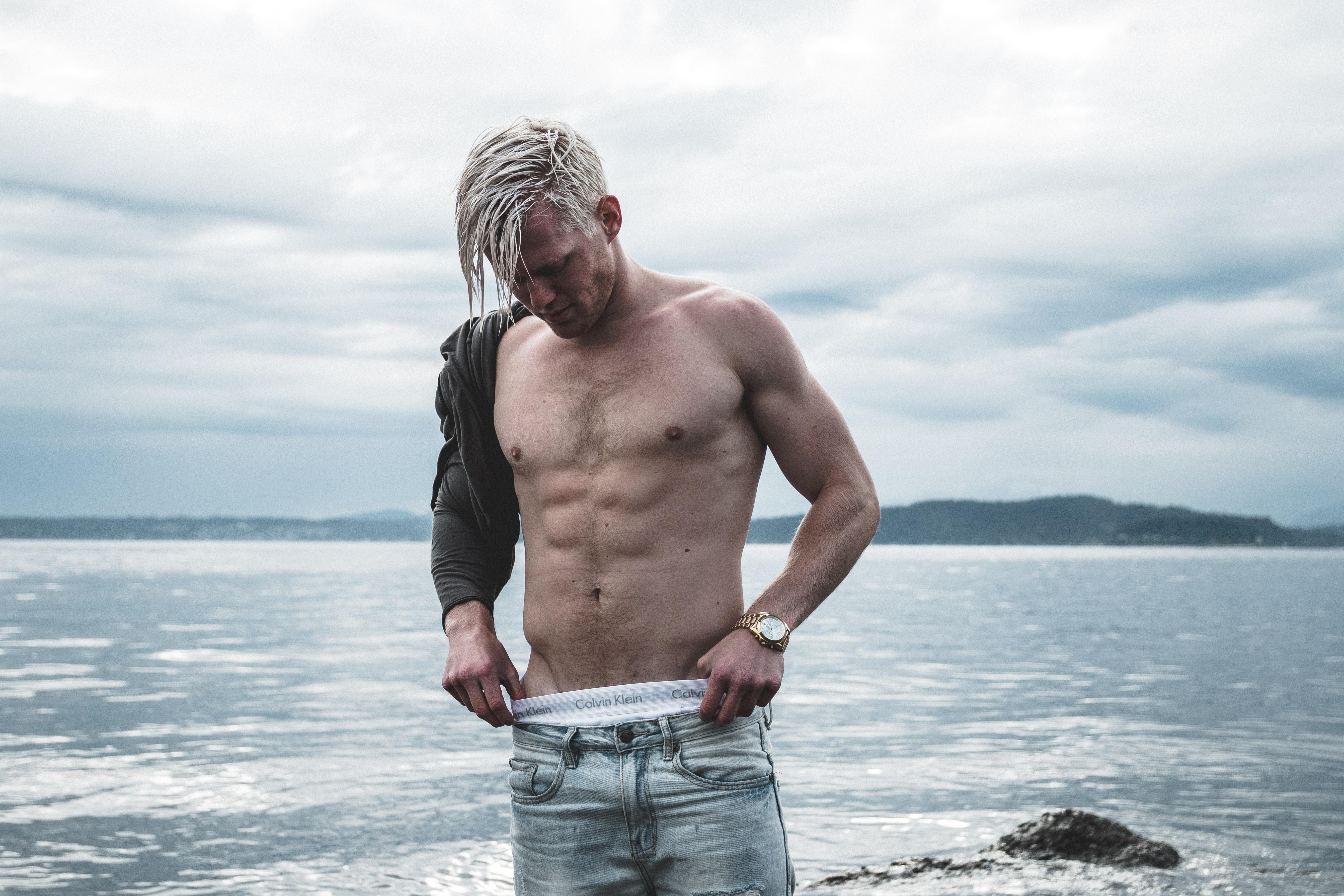 topless man wearing gray denim bottoms standing on shore at daytime