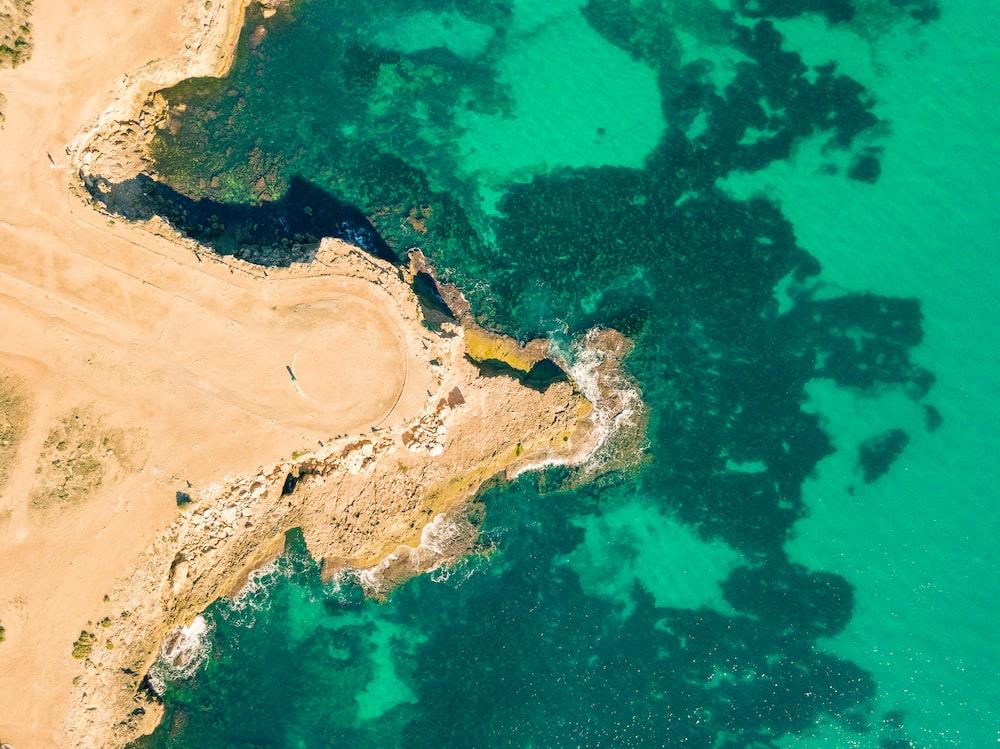 aerial photo of body of water beside brown dirt