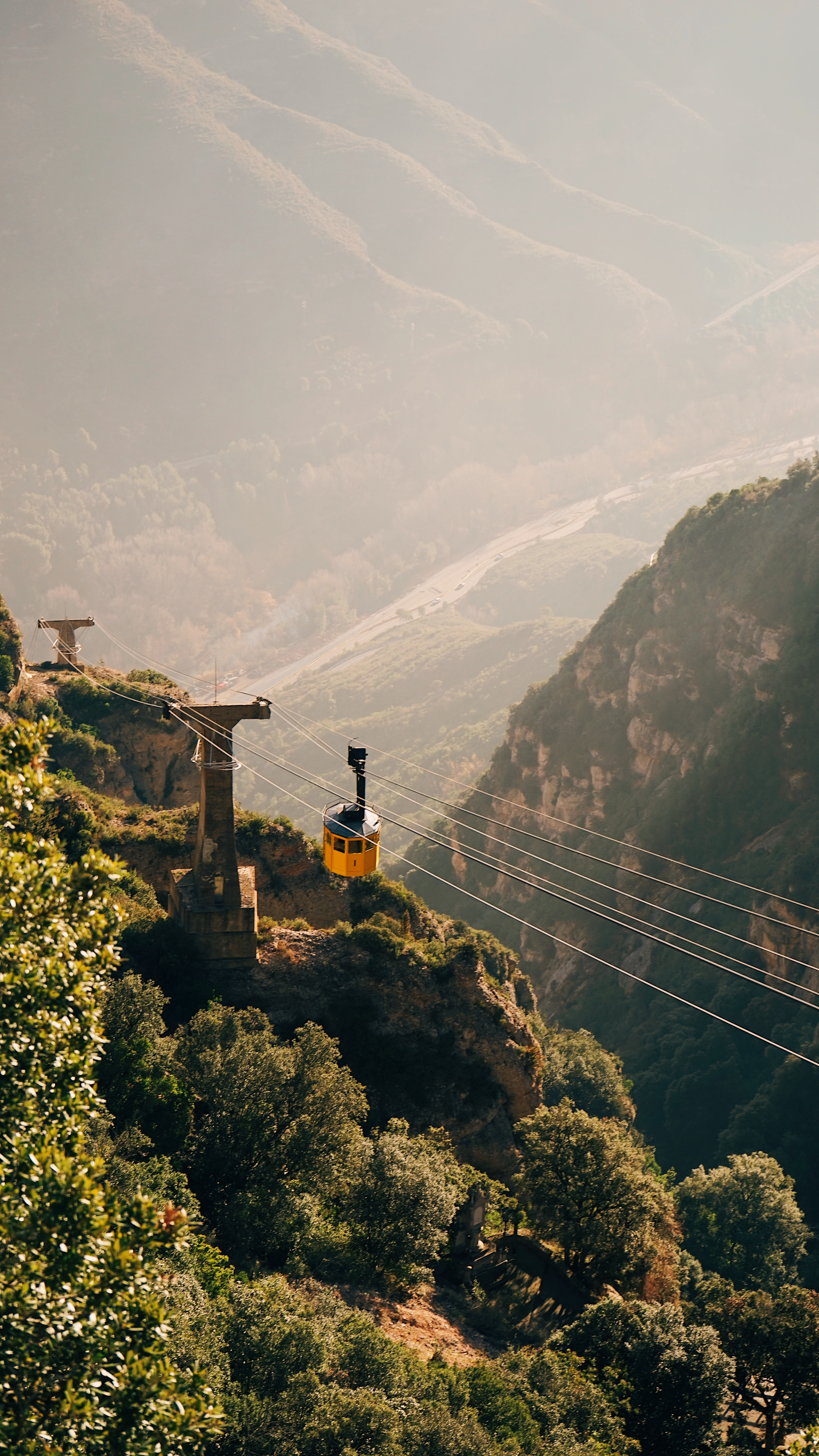 yellow cable car crossing mountains