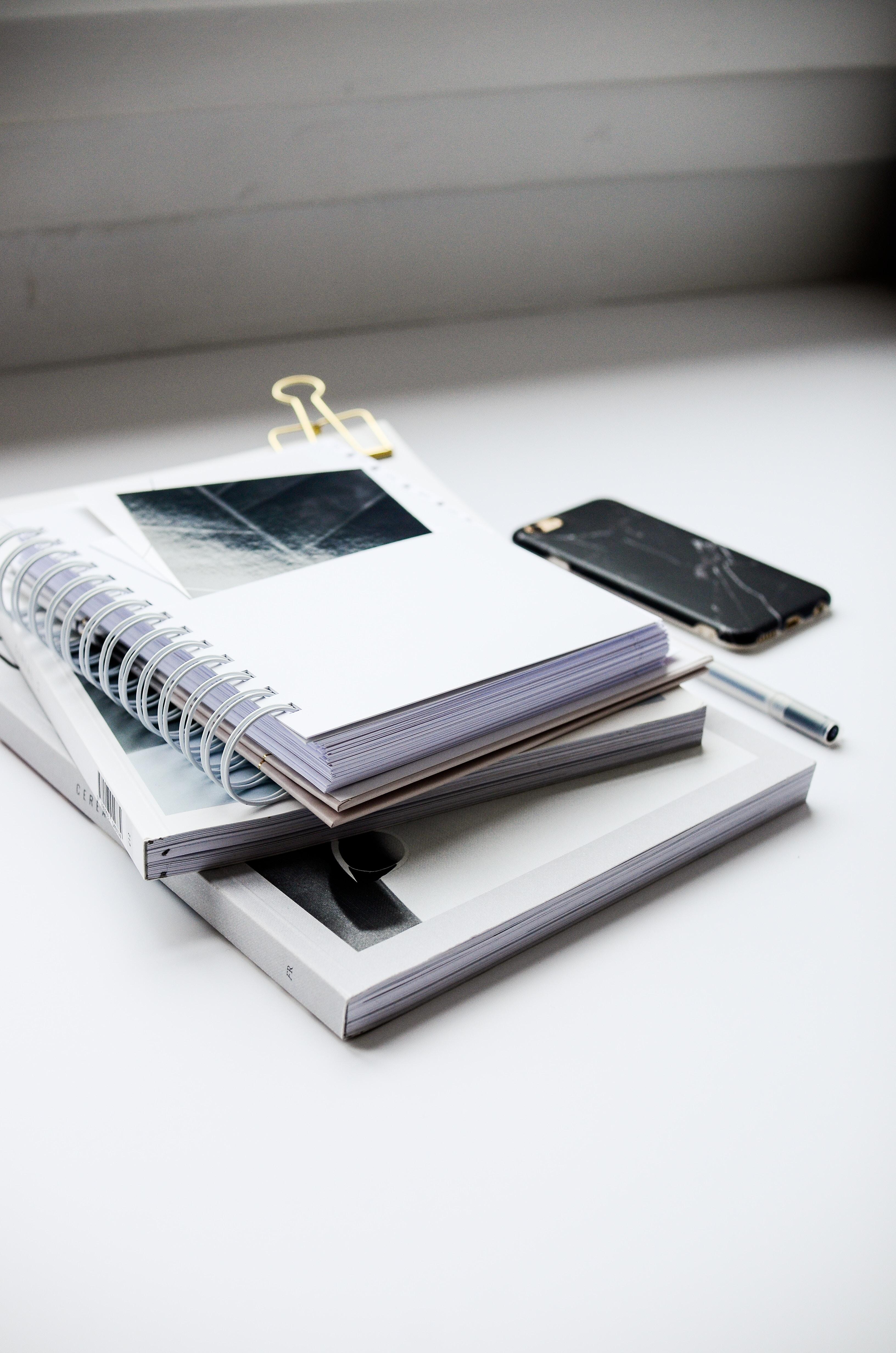broken smartphone beside sketch books