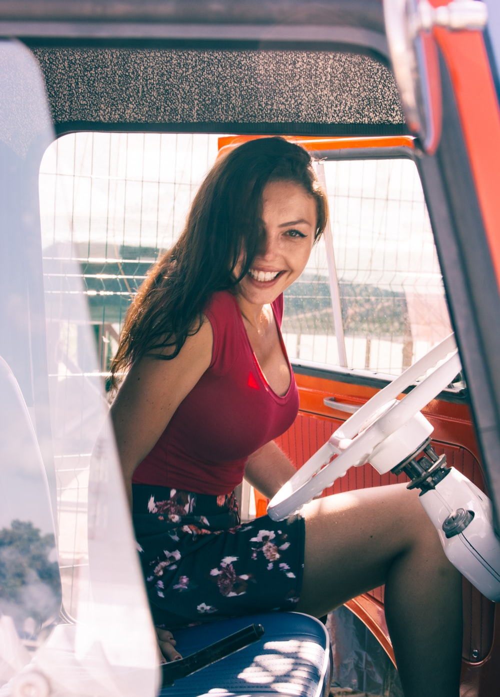 woman wearing red tank top and multicolored floral skirt while sitting inside vehicle