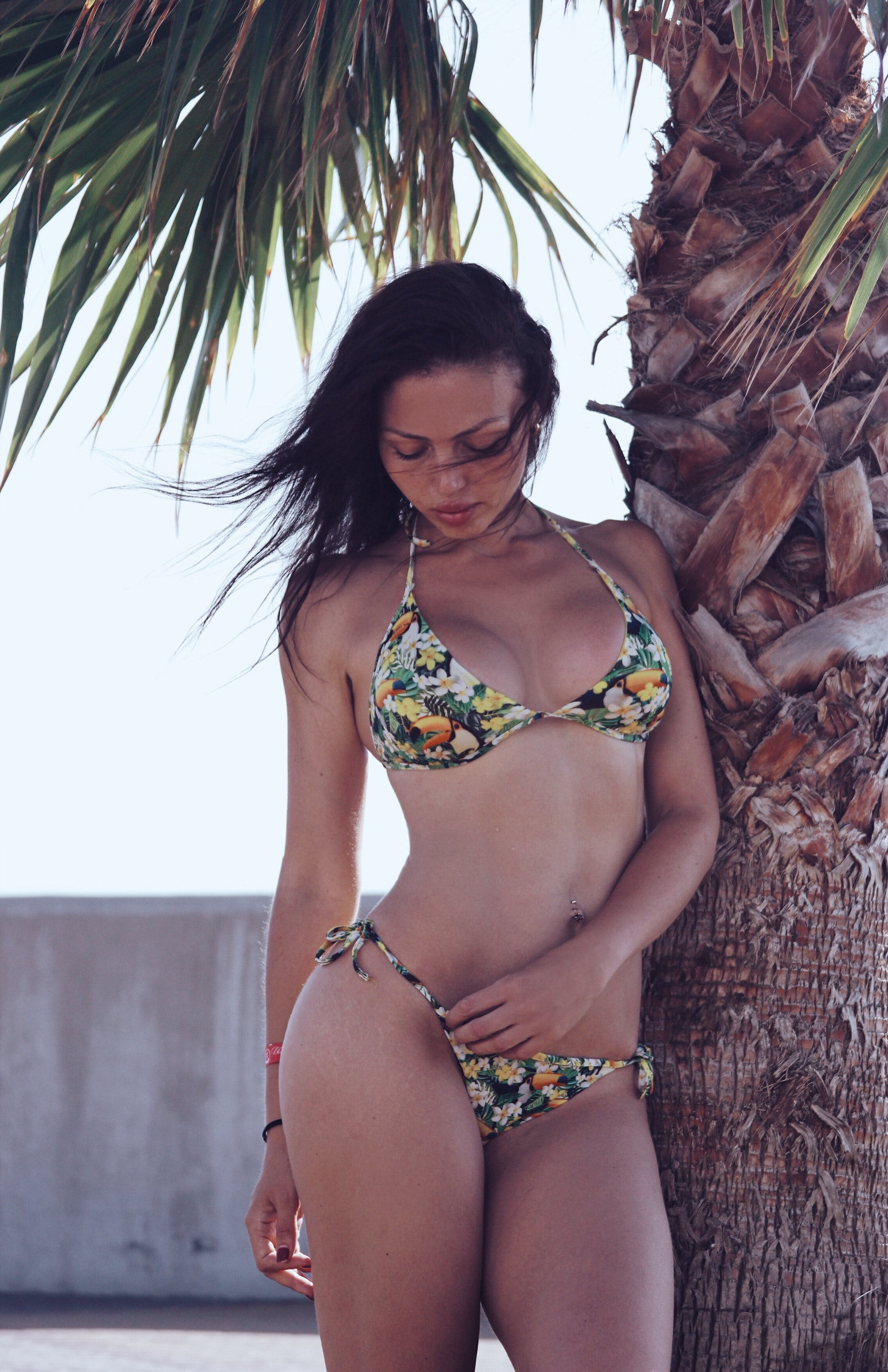 woman wearing floral bikini set standing beside palm tree at daytime