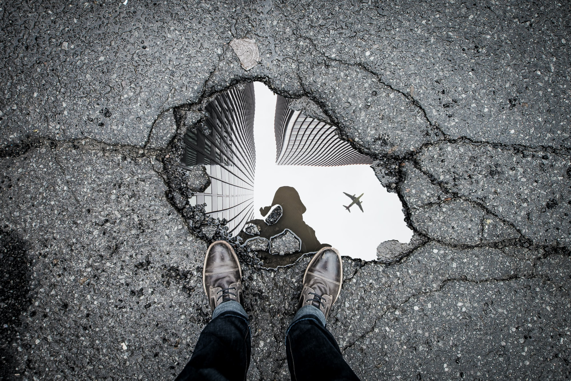 A shot of a puddle, which is reflecting tall buildings and an airplane.