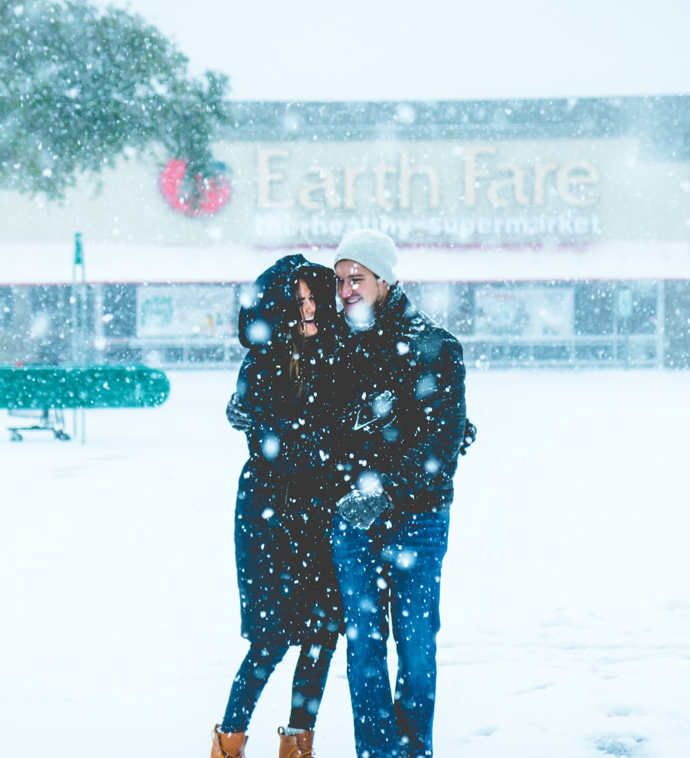 man and woman standing on snowing surface